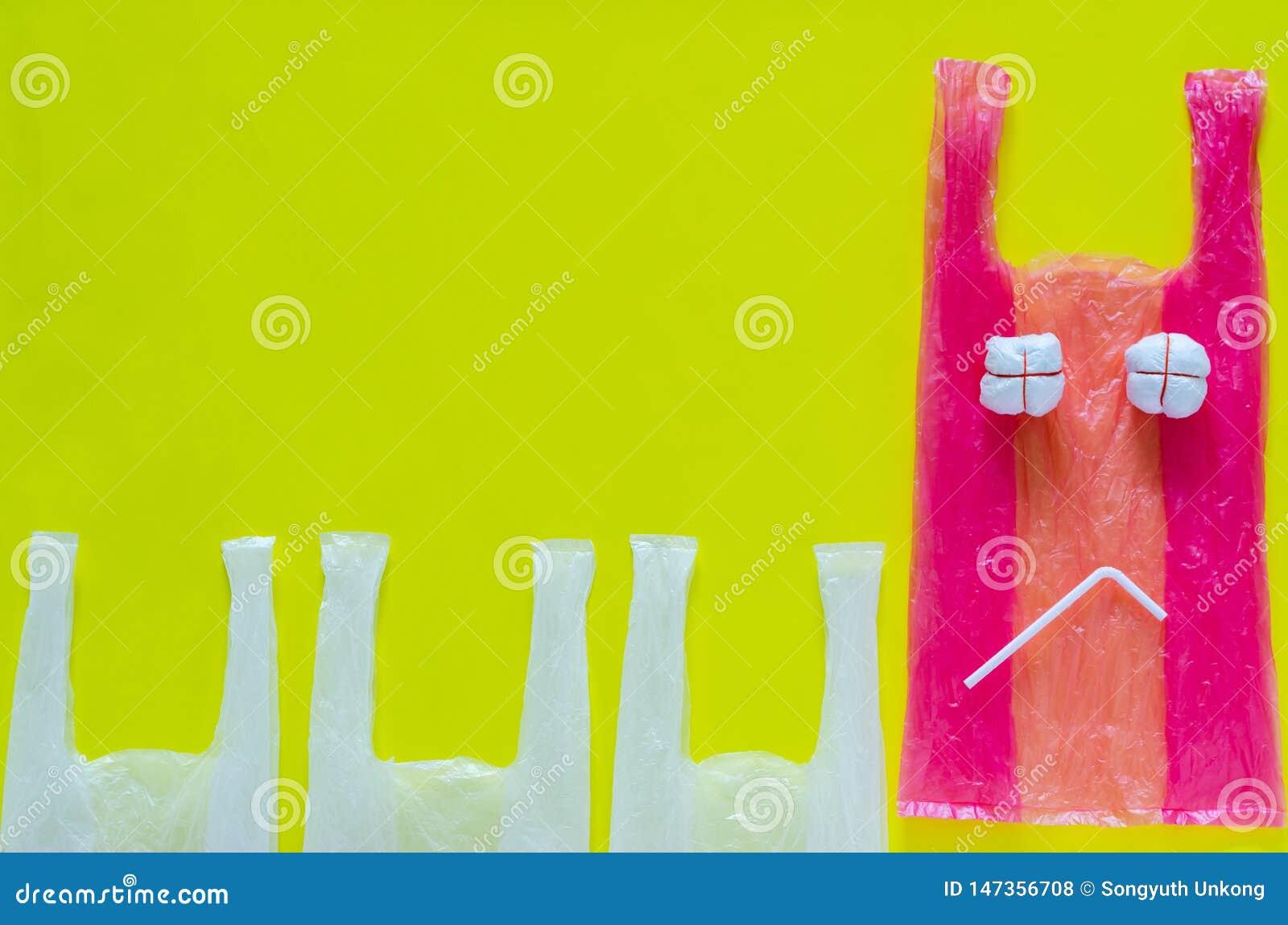Roze plastiek dat als ongelukkig uitdrukkingsgezicht wordt geplaatst met plastic stro voor einde die vijandige milieupakketten ge