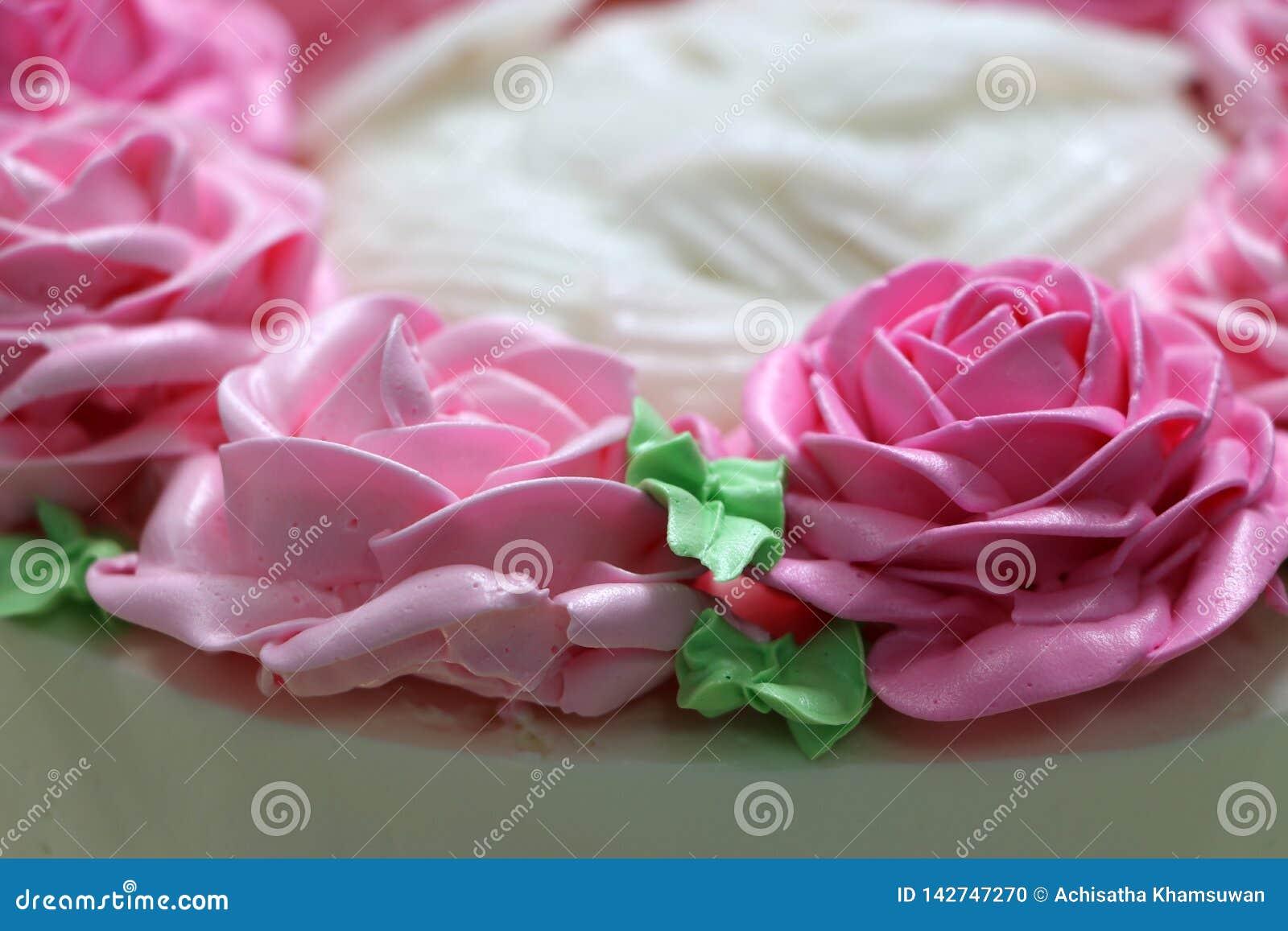 Roze rozen en groen blad van boterroom op de witte cake