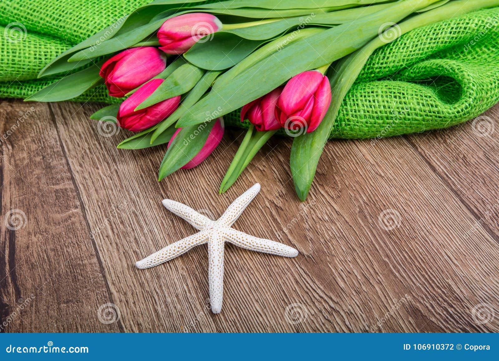 Rozgwiazda i tulipany na drewnianym stole