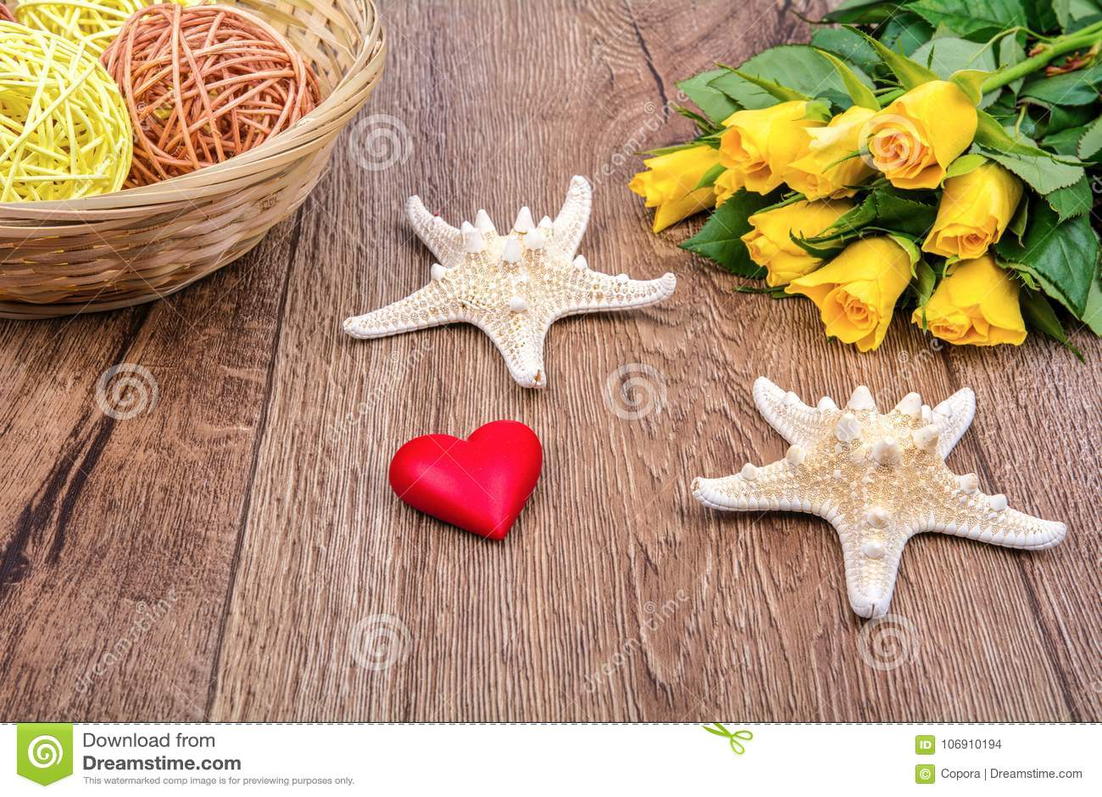 Rozgwiazdy, serce i róże na drewnianym stole,