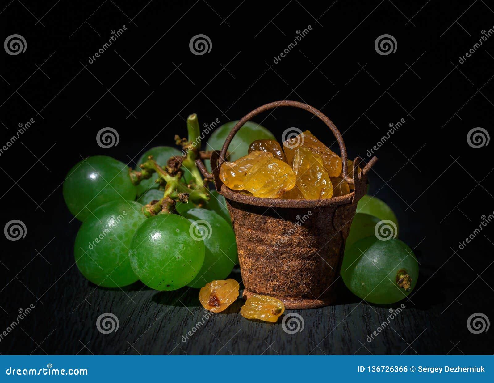 Rozijnen in een kleine emmer, druiven op een donkere achtergrond