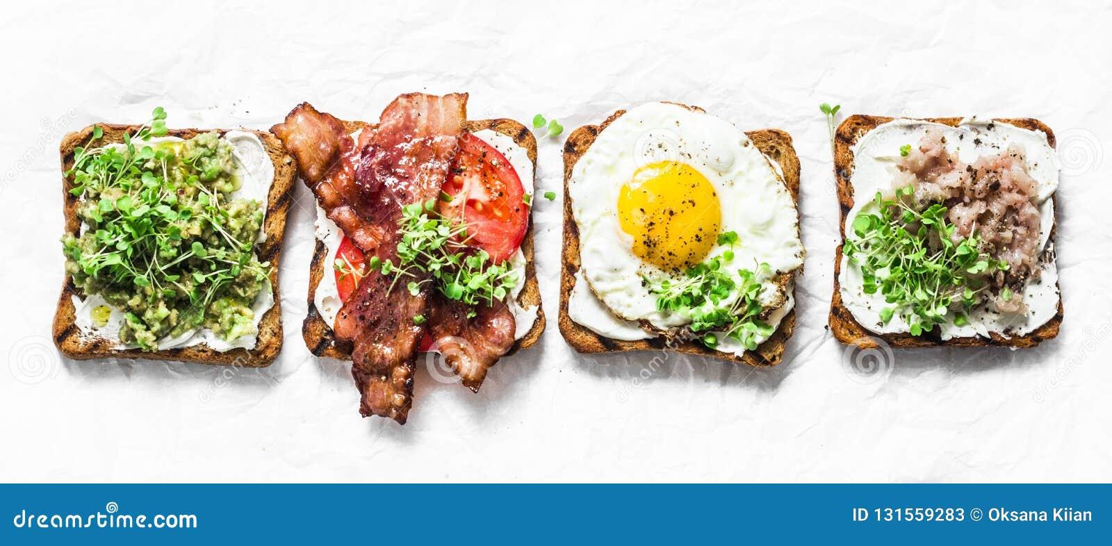 Rozmaitość kanapki dla śniadania, przekąska, zakąski - avocado puree, smażył jajko, pomidory, bekon, ser, uwędzona makrela