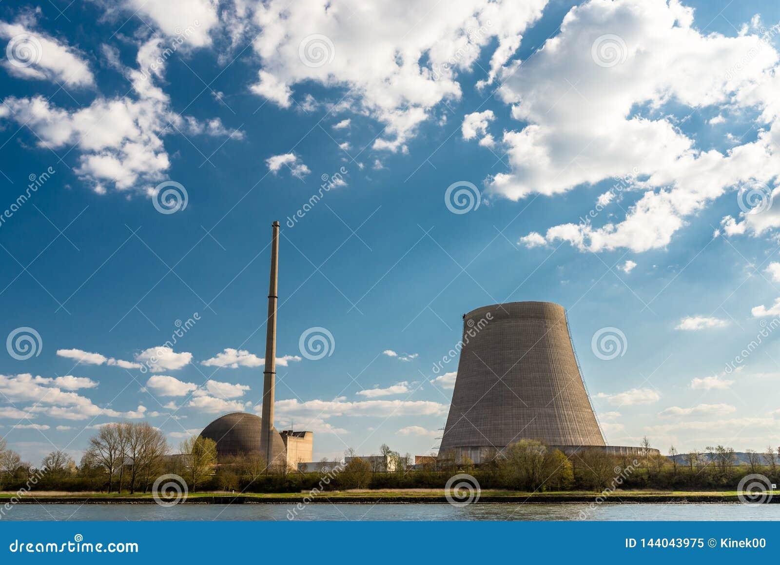 Rozmontowywający jądrowy atomowy komin przeciw niebieskiemu niebu z chmurami w Mulheim-Karlich w zachodnim Niemcy na Rhine rzece,