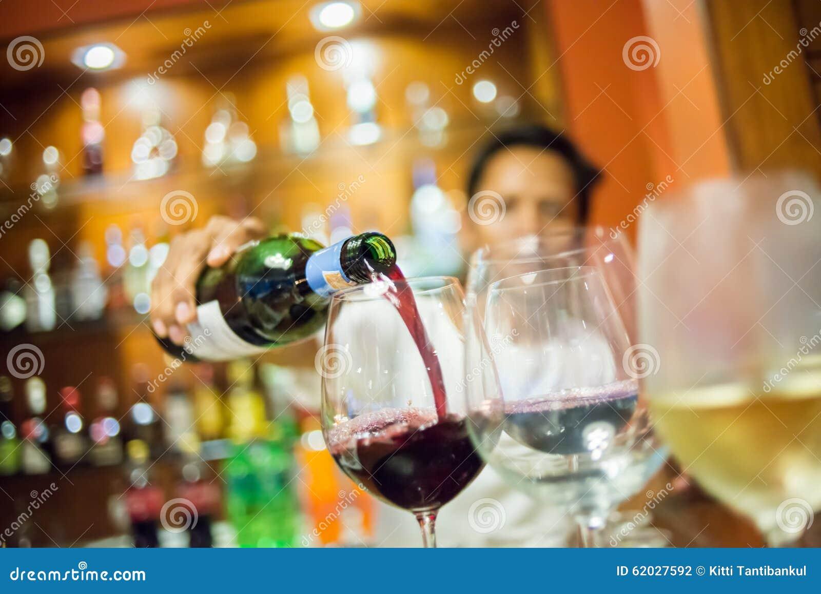 Rozmyty mężczyzna dolewania czerwone wino w szkło z białego wina foregroun