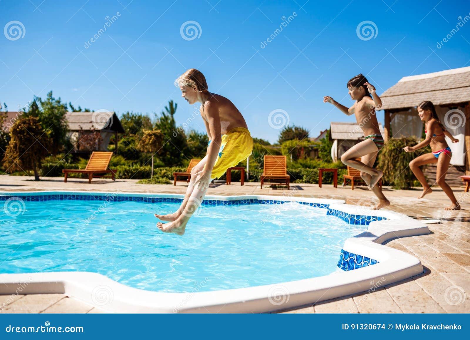 Rozochoceni dzieci raduje się, skaczący, pływający w basenie
