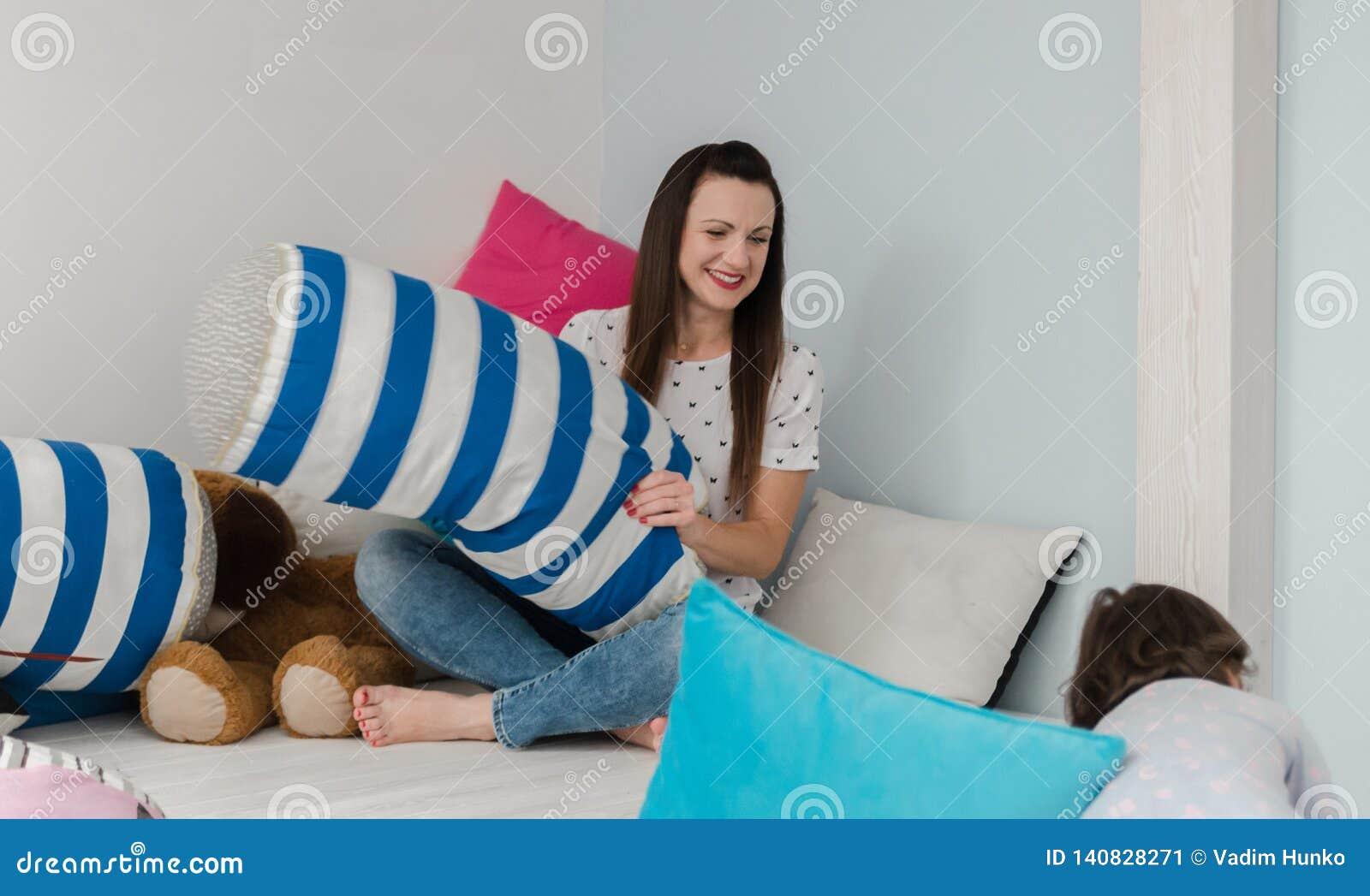 Rozochoceni dzieciaki i rodzice ma poduszki walkę na łóżku w domu
