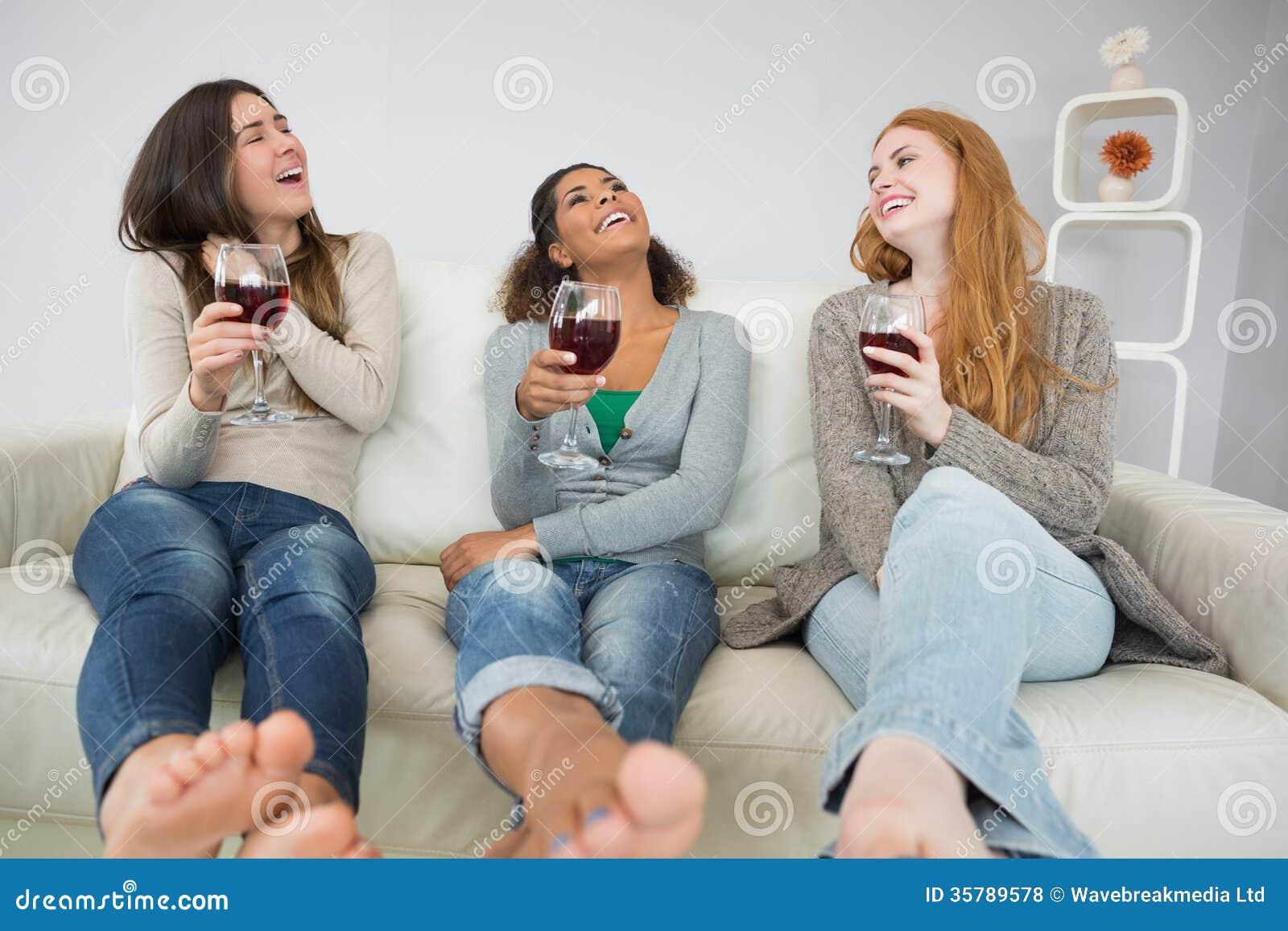 Rozochoceni młodzi żeńscy przyjaciele z win szkłami w domu