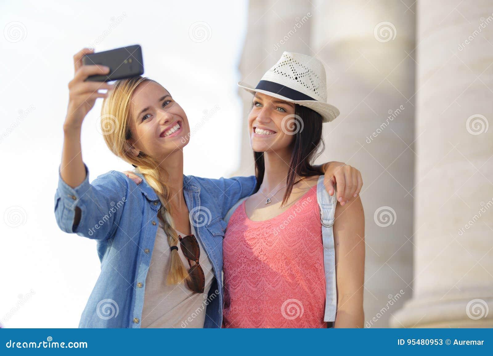 Rozochoceni turystyczni żeńscy przyjaciele bierze fotografie themselves