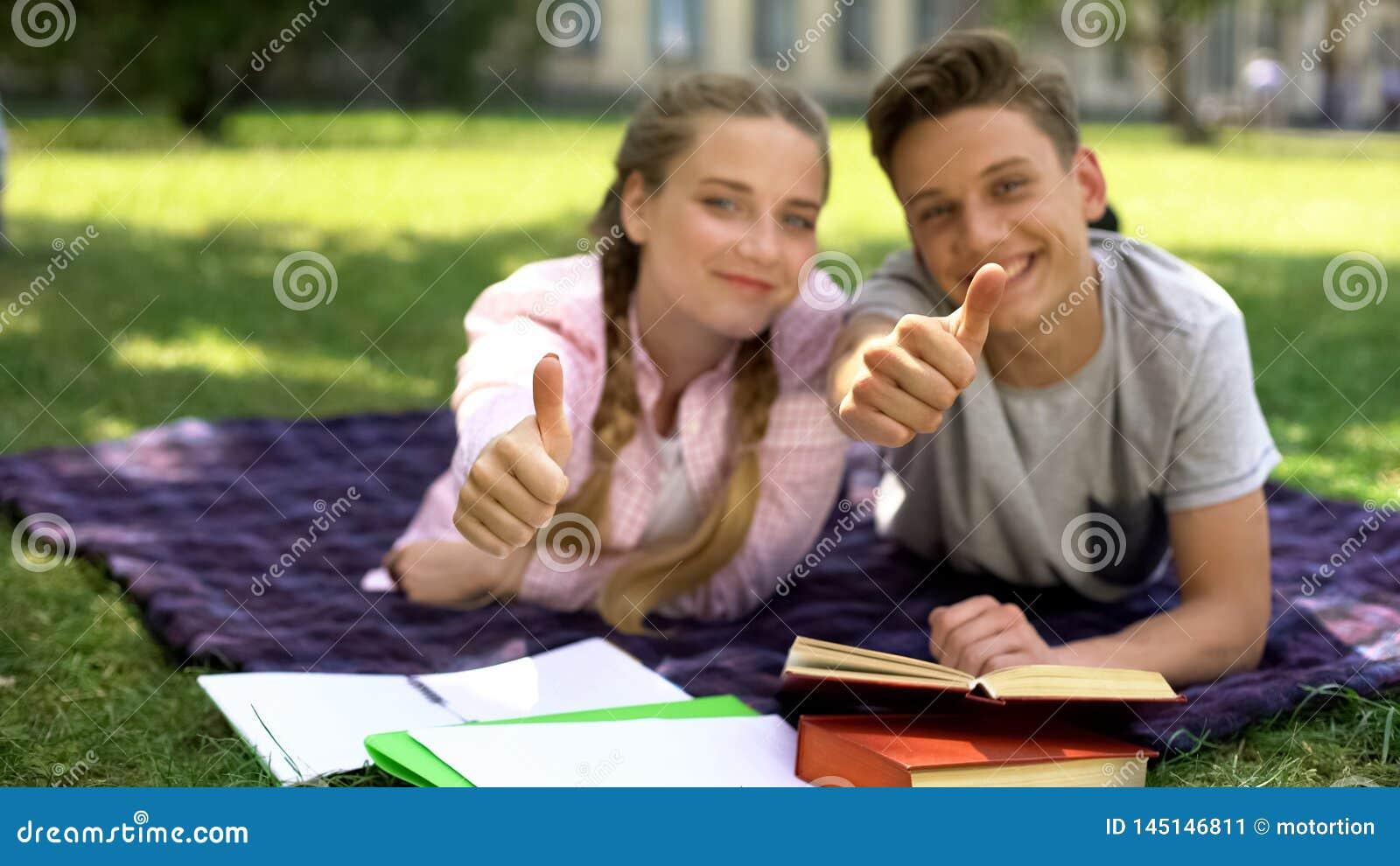 Rozochoceni ucznie pokazuje aprobaty i patrzeje kamer?, odleg?a edukacja