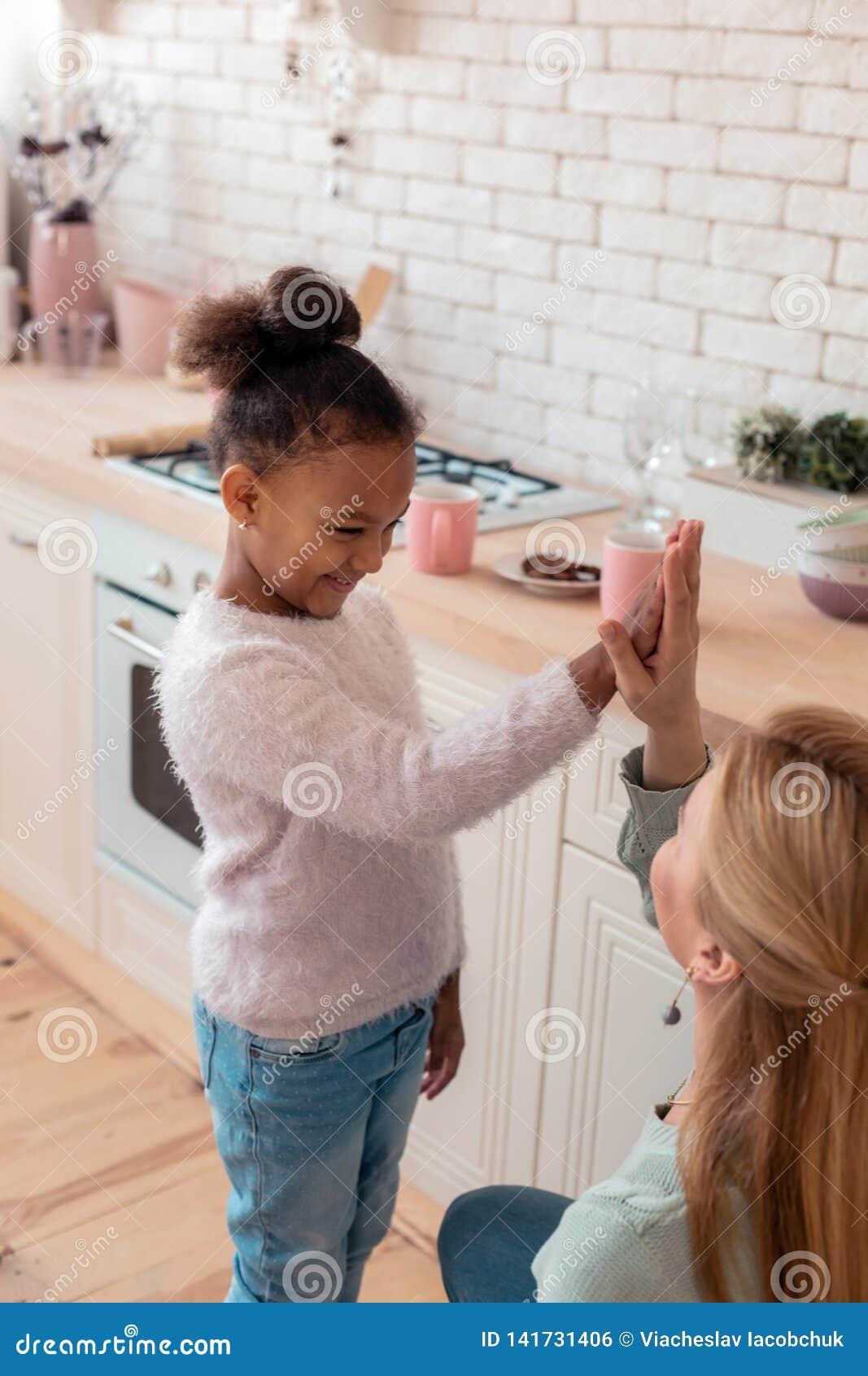 Rozochocona śmieszna dziewczyna daje wysokości pięć jej kochająca matka