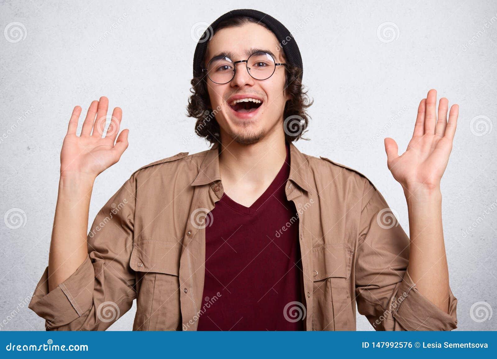 Rozochocona atrakcyjna modniś pozycja odizolowywająca nad białym tłem w studiu, dźwiganie jego ręki w górę, być w wysokich duchac