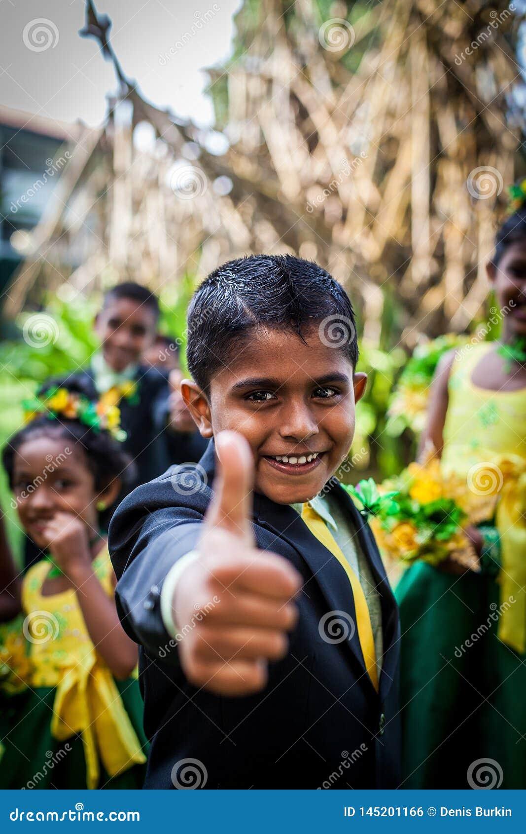 Rozochocona Azjatycka chłopiec w kostiumu pokazuje jego kciuk w górę tła inni dzieci przeciw