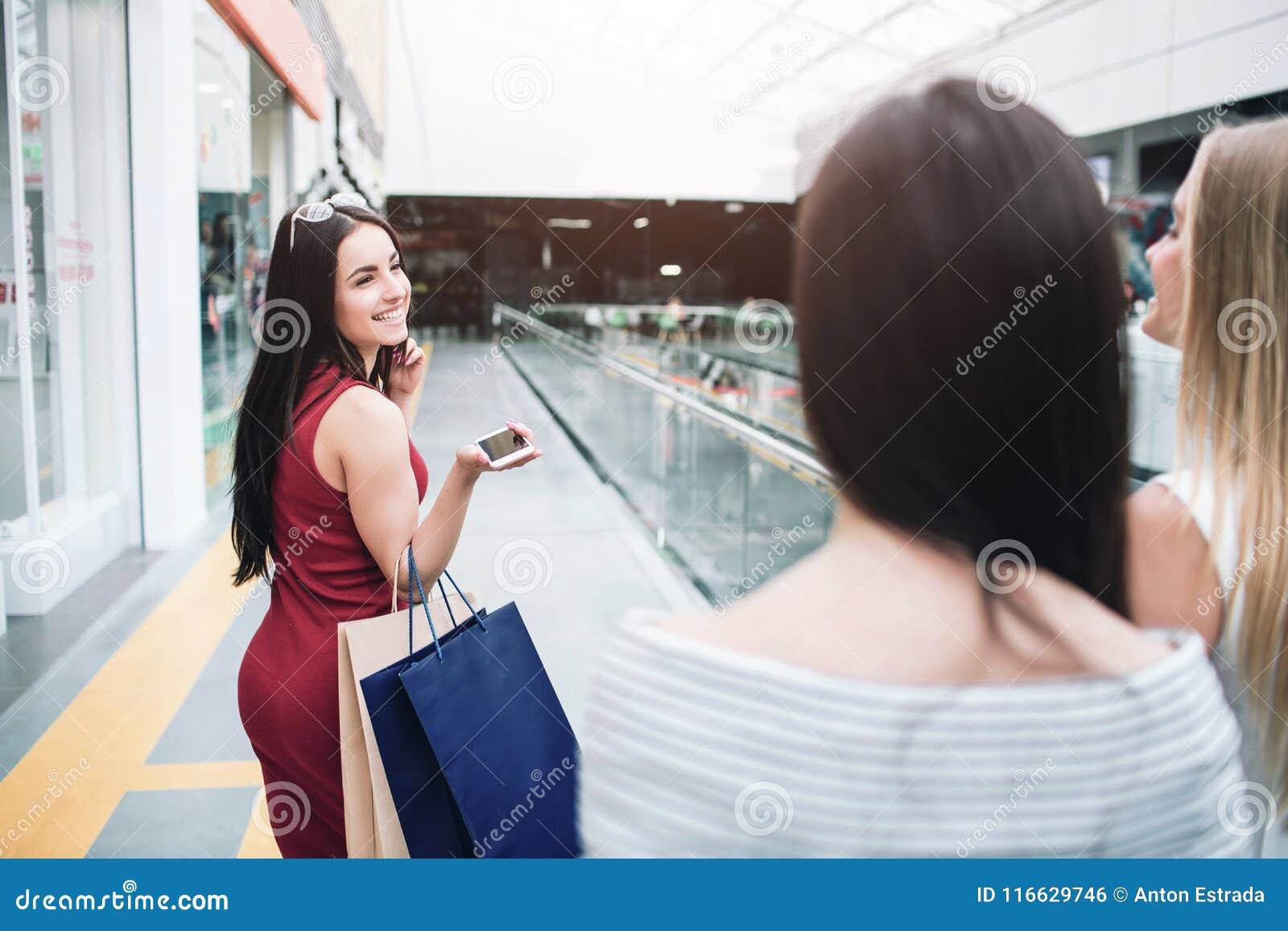 Rozochocona i piękna dziewczyna w czerwieni sukni jest przyglądająca jej ono uśmiecha się i przyjaciele z powrotem Także trzyma d