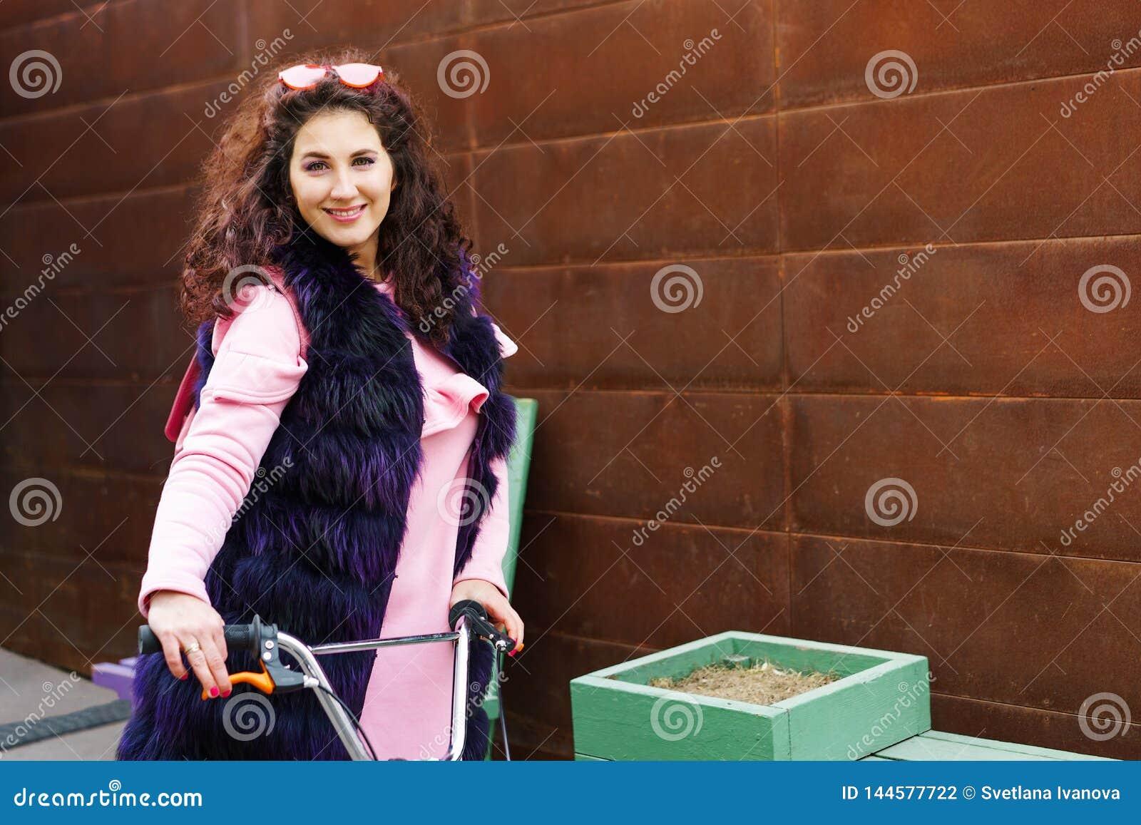 Rozochocona kobieta jedzie hulajnogę w różowej sukni purpura futerkowym przylądku i