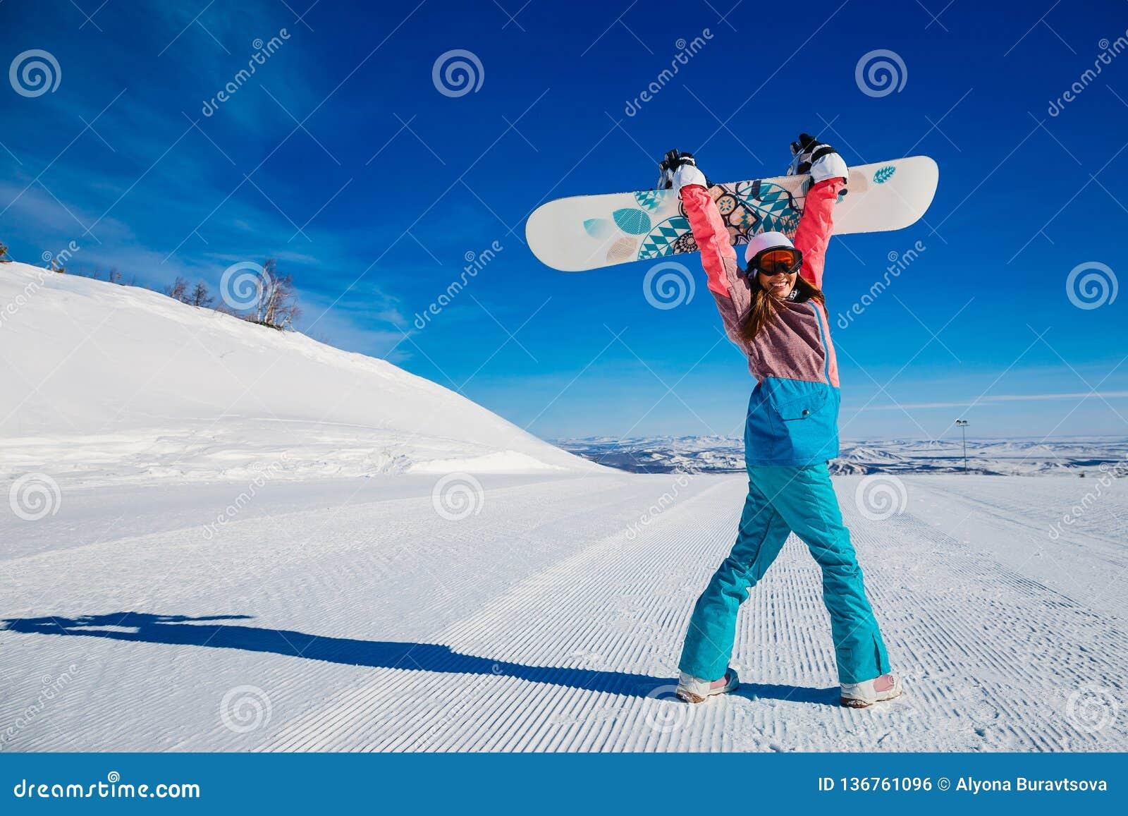 Rozochocona kobieta z jazdą na snowboardzie w górach w zimie