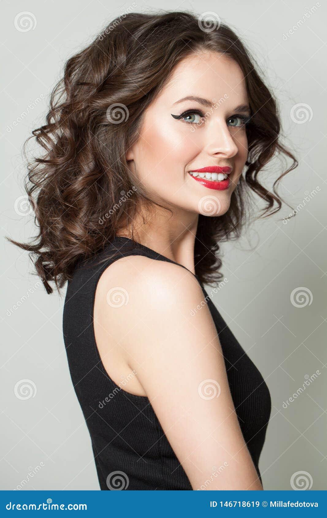 Rozochocona kobieta z makeup i kędzierzawym włosy Ładny wzorcowy ono uśmiecha się