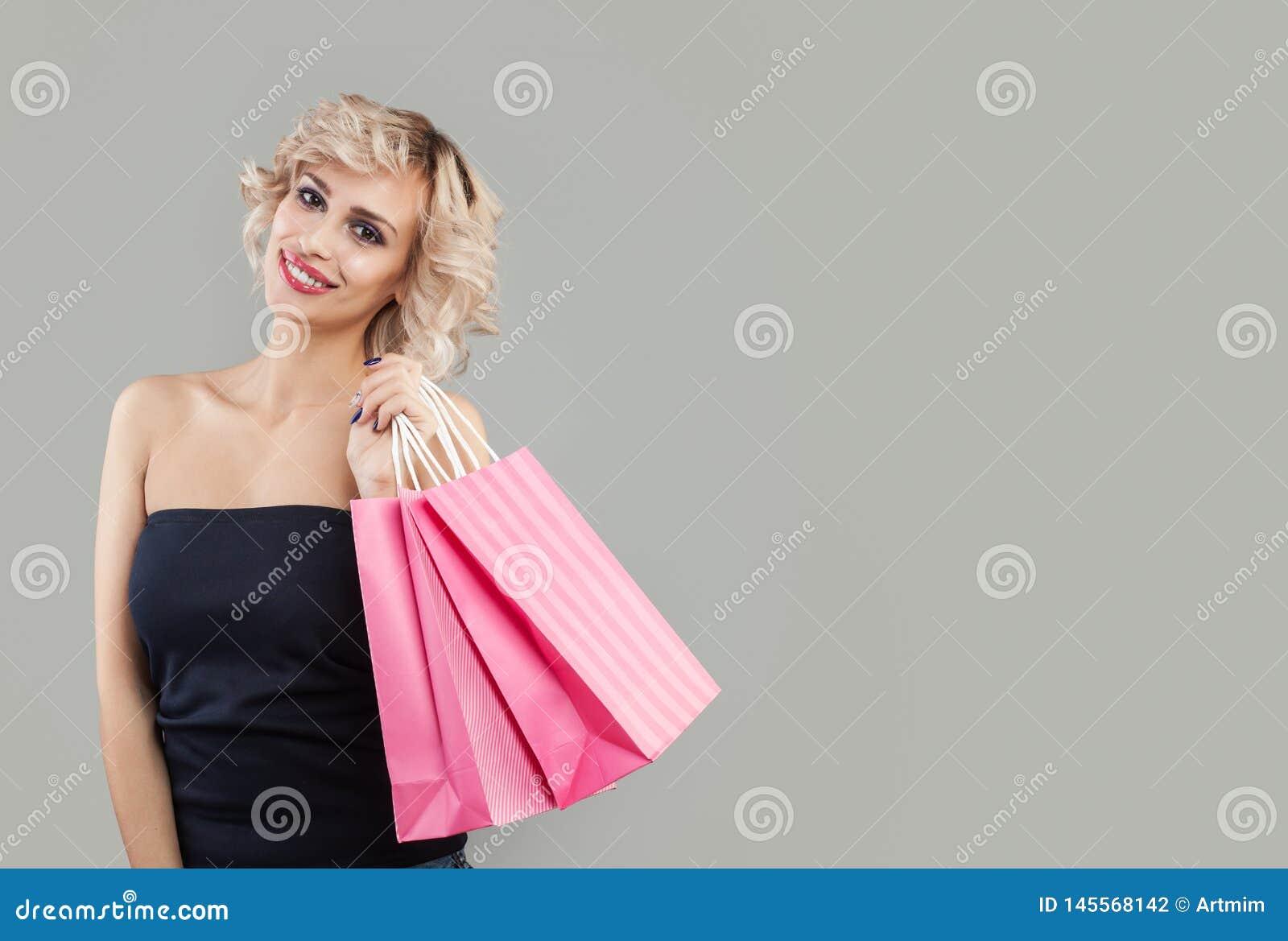 Rozochocona kobieta z torbami na zakupy, portret Piękny model z makeup i krótkim ostrzyżeniem
