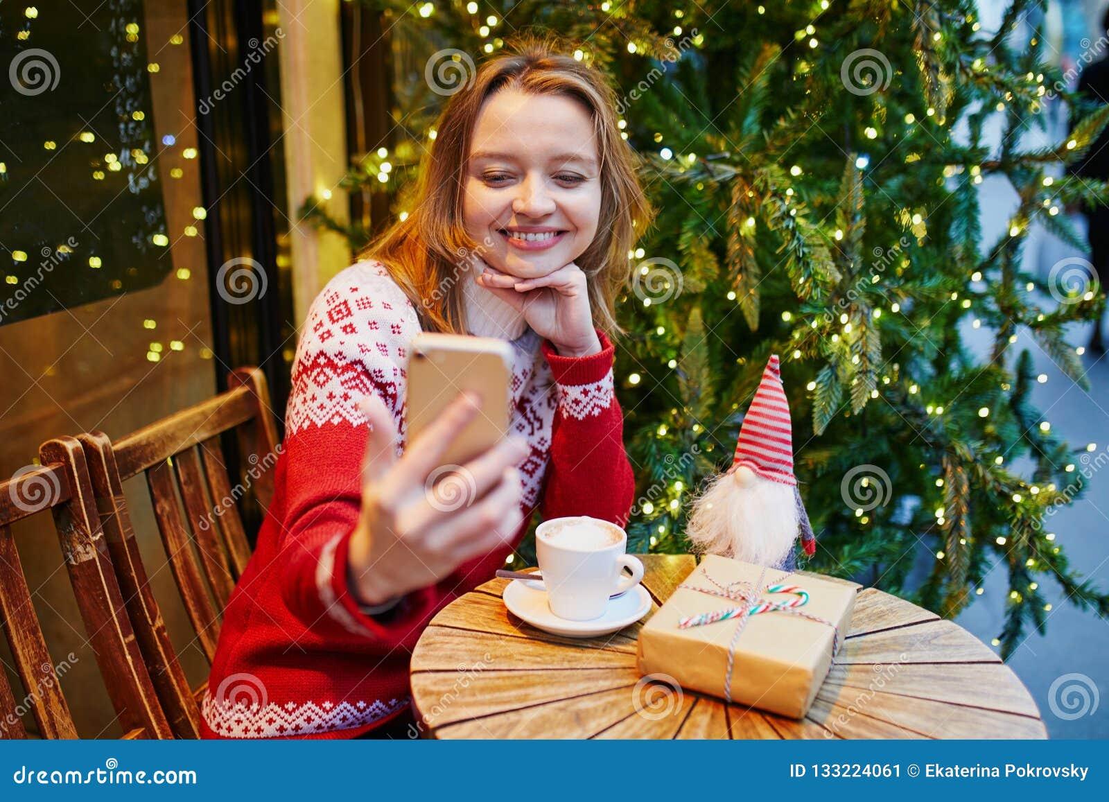 Rozochocona młoda dziewczyna w wakacyjnym pulowerze w kawiarni dekorował dla bożych narodzeń