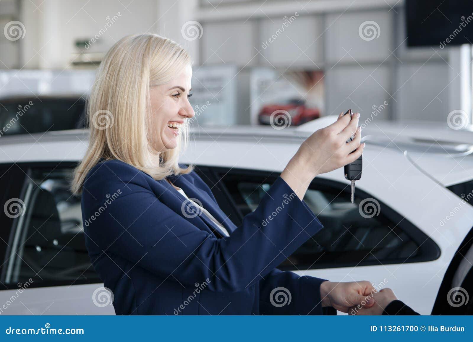Rozochocona młoda kobieta otrzymywa nowych samochodowych klucze w samochodzie robi zakupy
