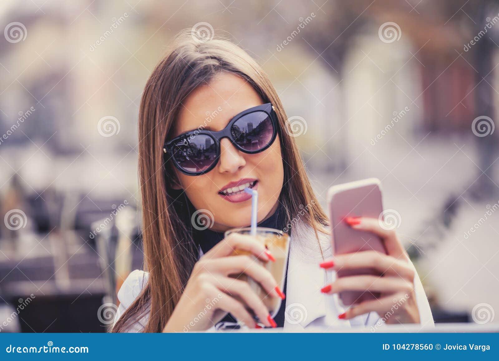 Rozochocona młoda kobieta trzyma mądrze telefon i pije gorącego choco