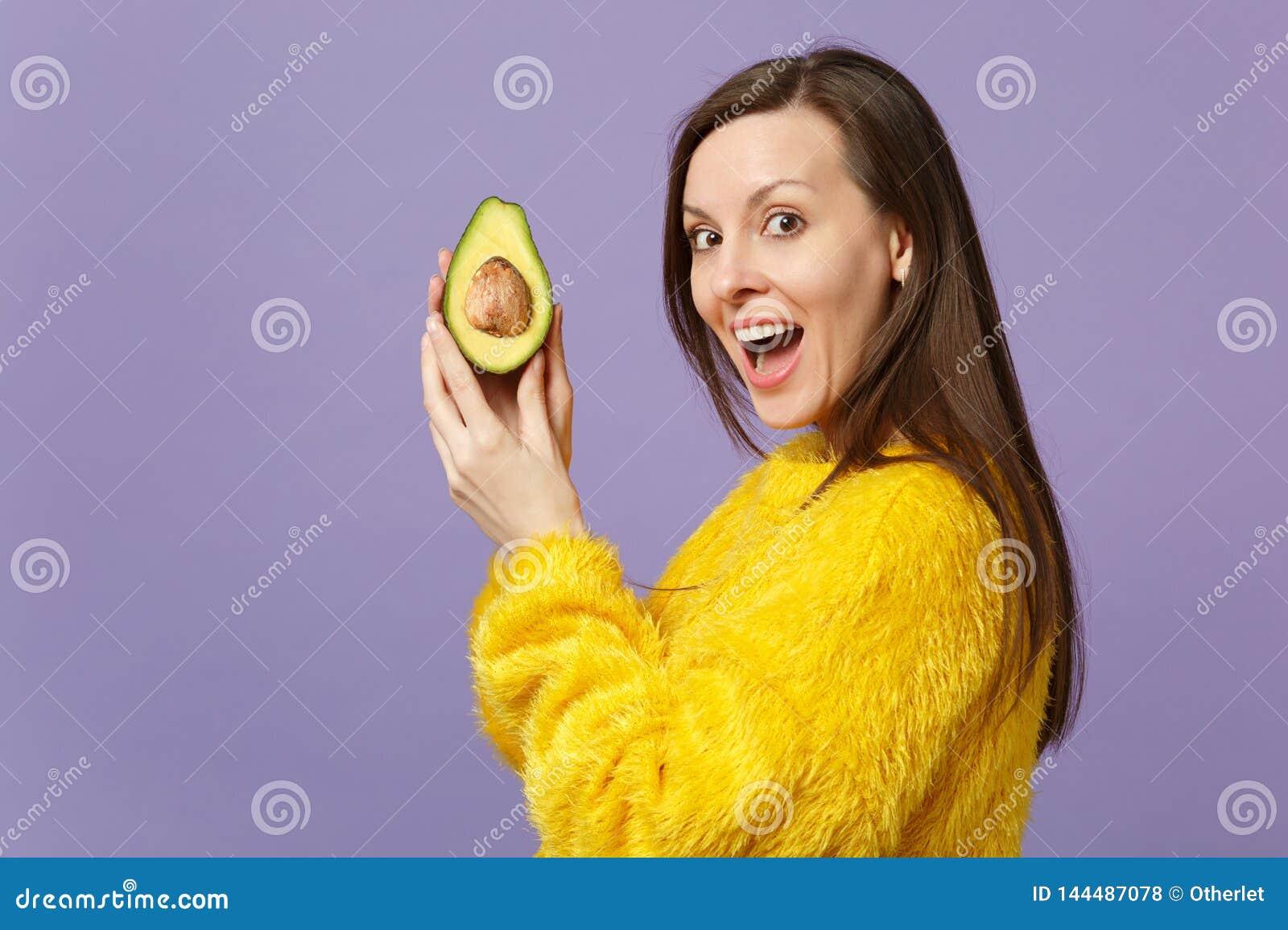Rozochocona młoda kobieta utrzymuje usta otwartą trzyma połówkę świeży dojrzały zielony avocado odizolowywający na fiołku w futer