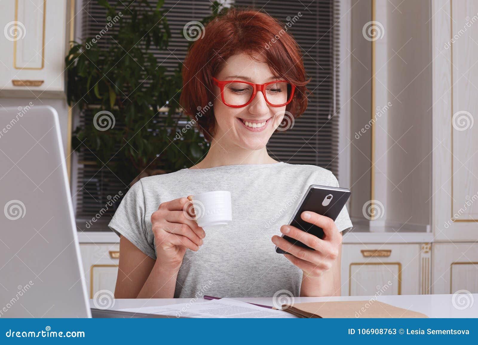 Rozochocona modna kobieta z czerwonym włosy, uradowanym przeglądać fotografie na ogólnospołecznych stronach internetowych, kawową