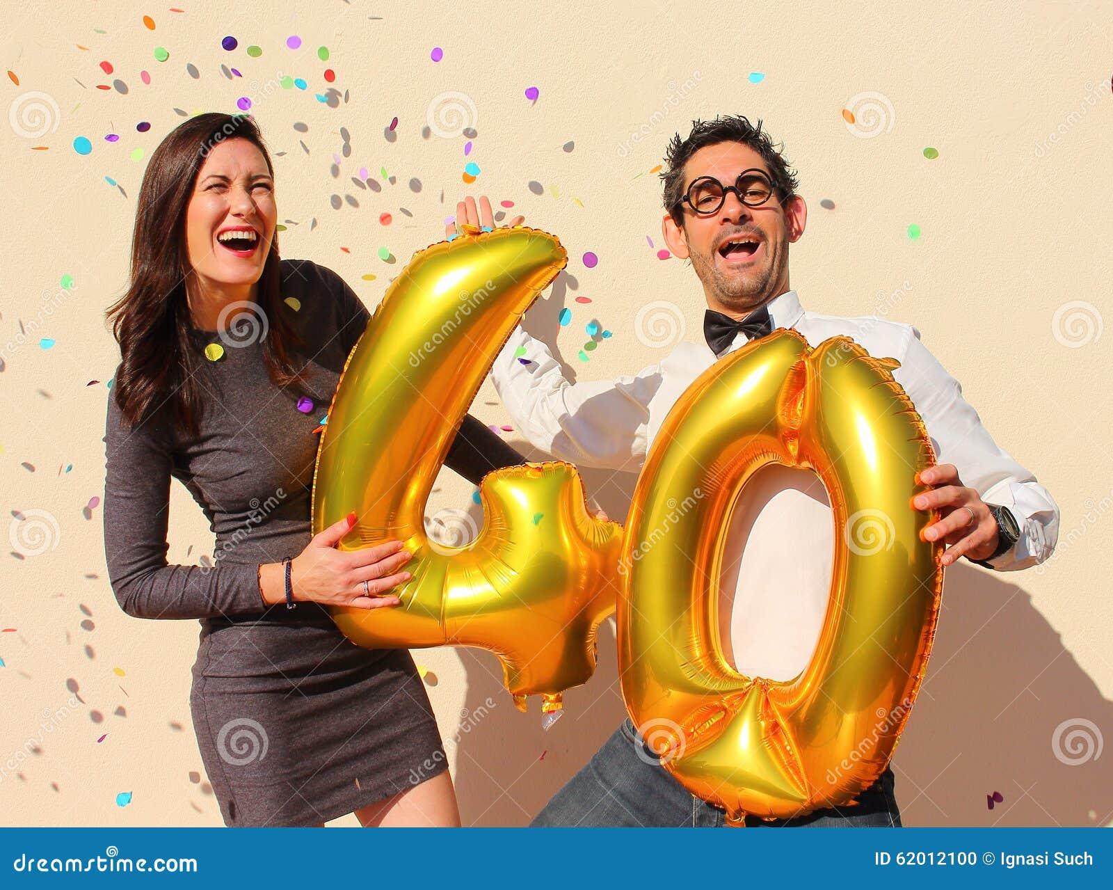 Rozochocona para świętuje czterdzieści rok urodzinowych z dużymi złotymi balonami i kolorowymi małymi kawałkami papieru w powietr