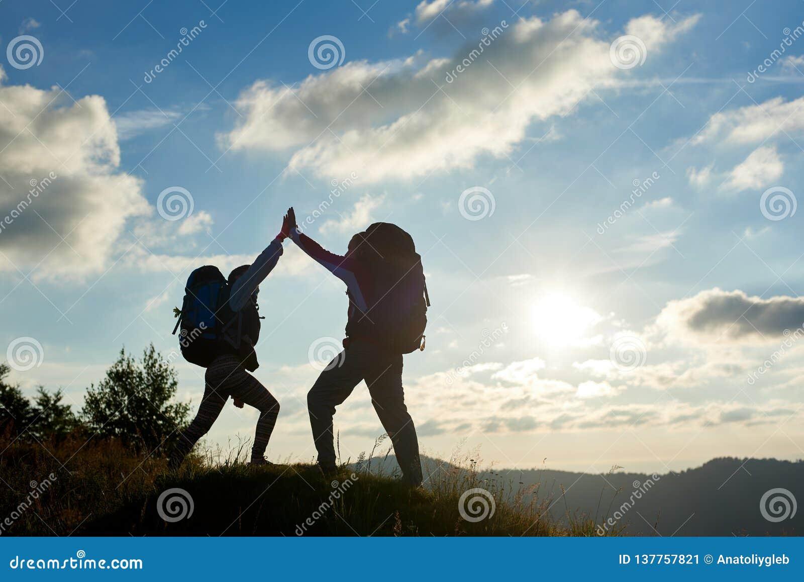 Rozochocona para z plecakami na górze góry daje each inni wysocy pięć przeciw zmierzchowi