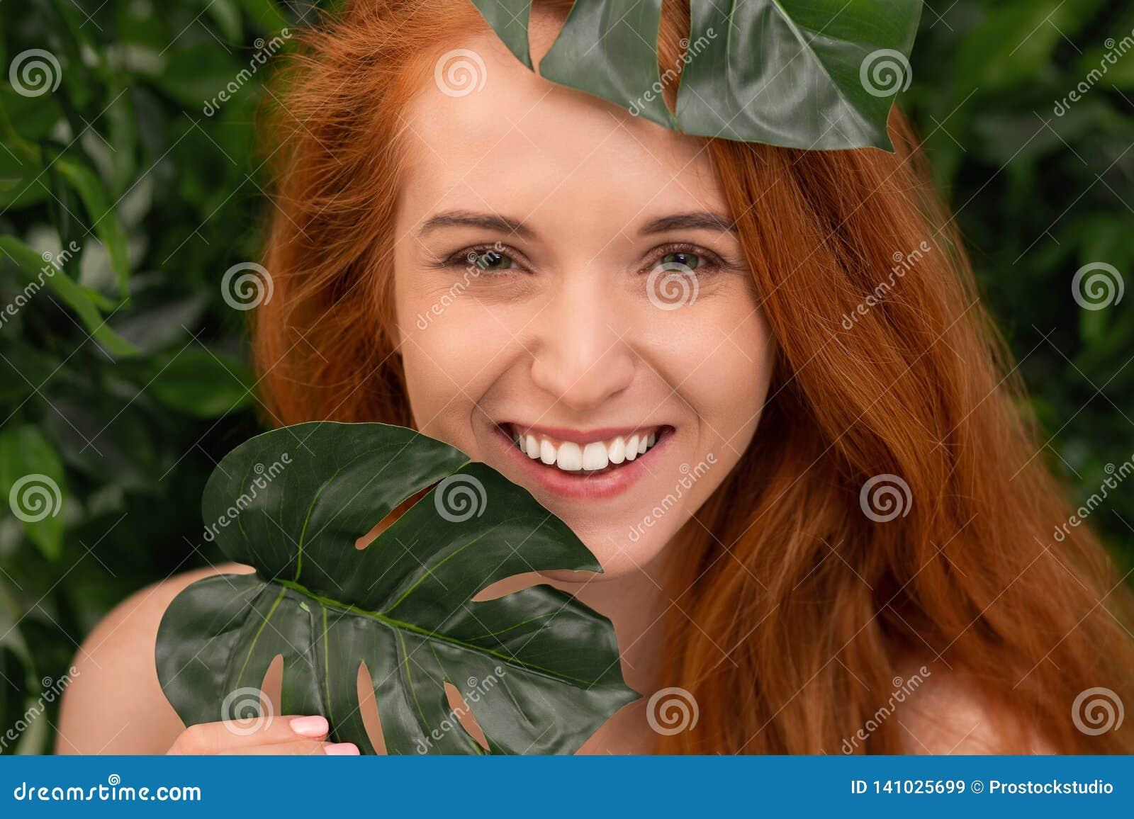 Rozochocona rudzielec kobieta śmia się przez monstera liści