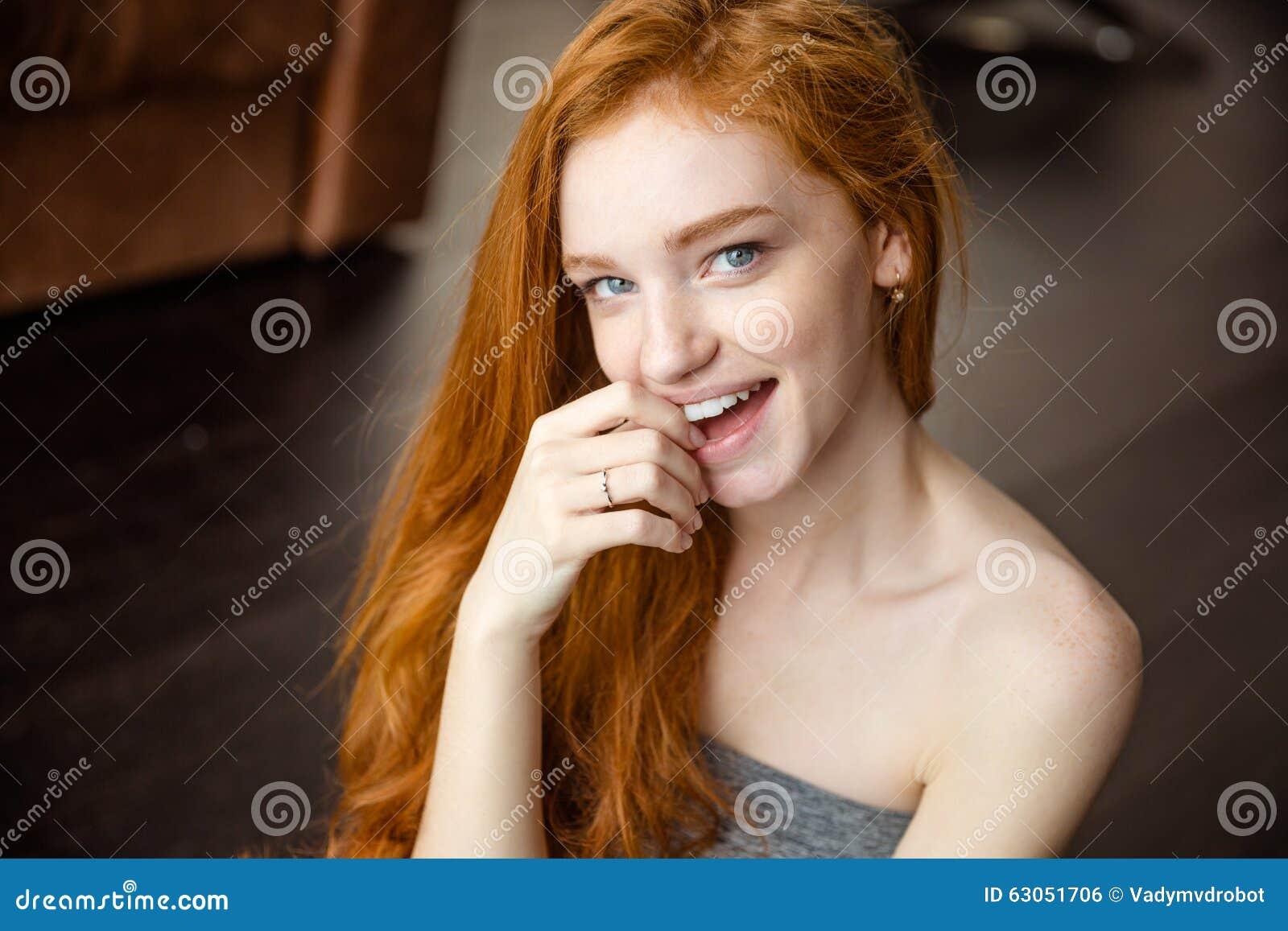 Rozochocona rudzielec kobieta patrzeje kamerę