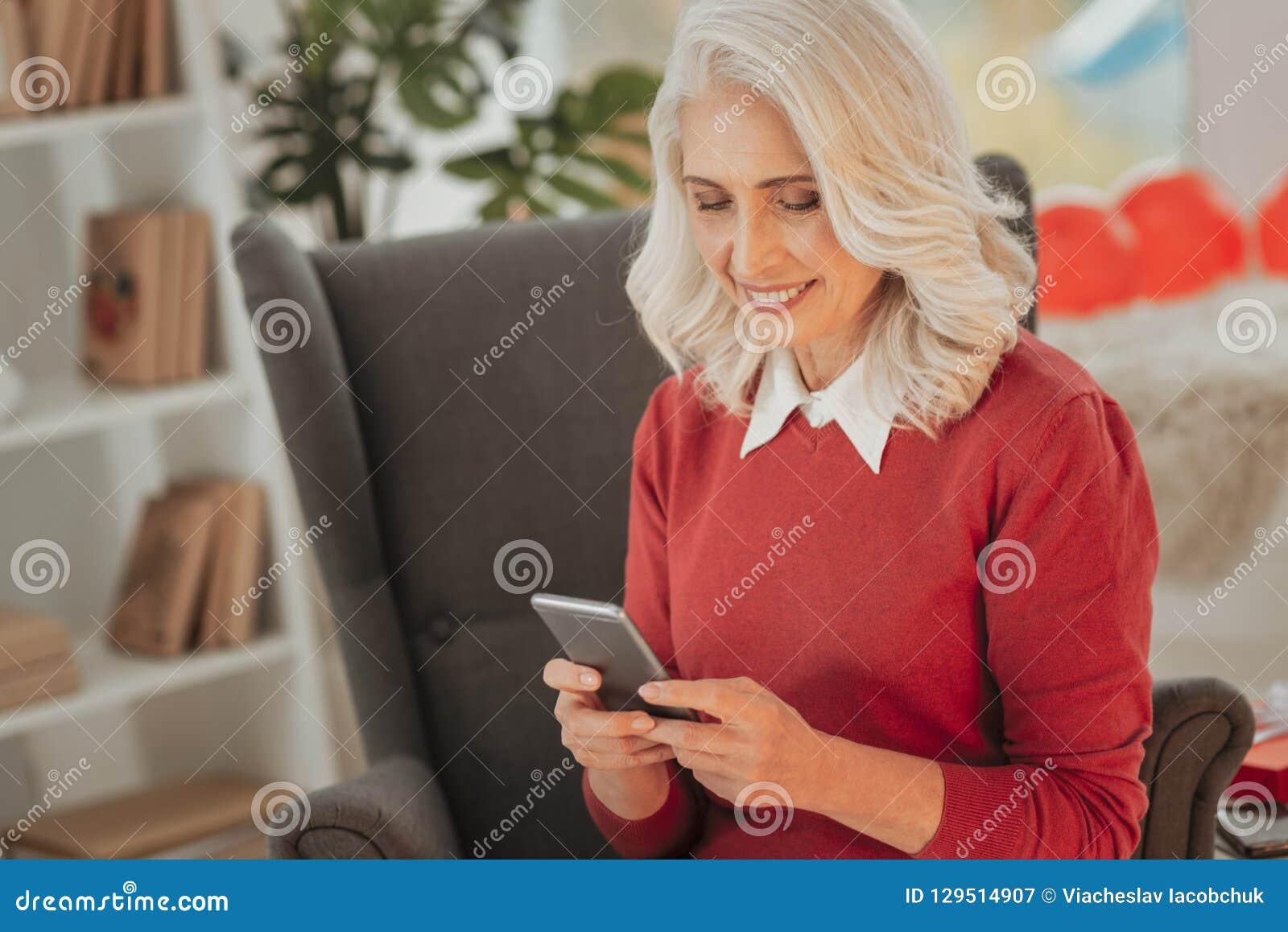 Rozochocona starsza dama wyszukuje śmiesznych miejsca na smartphone