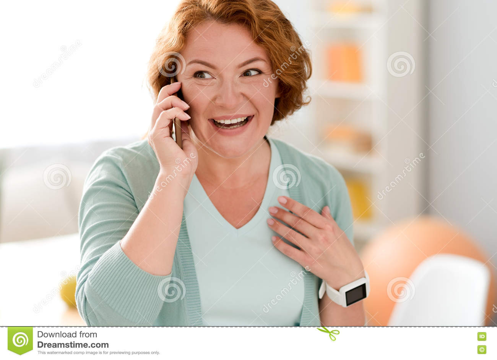 Rozochocona starsza kobieta opowiada na telefonie komórkowym