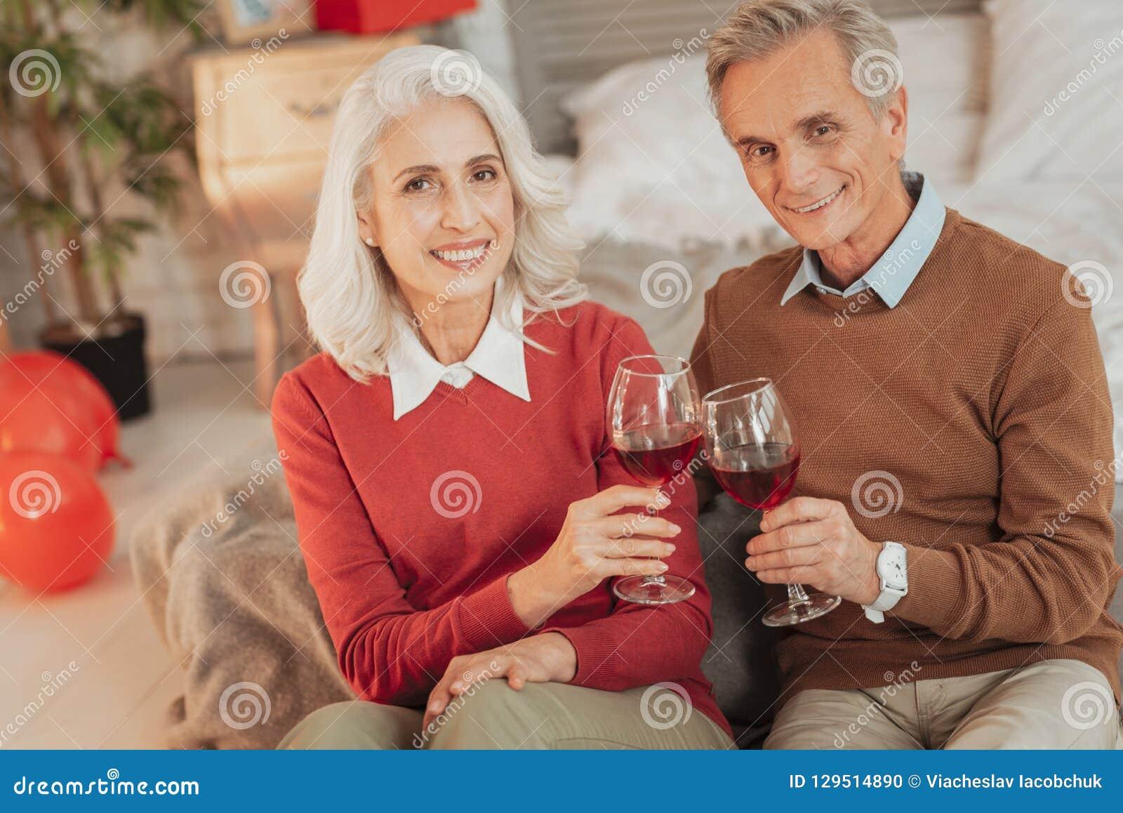 Rozochocona starsza para ma romantycznego gościa restauracji