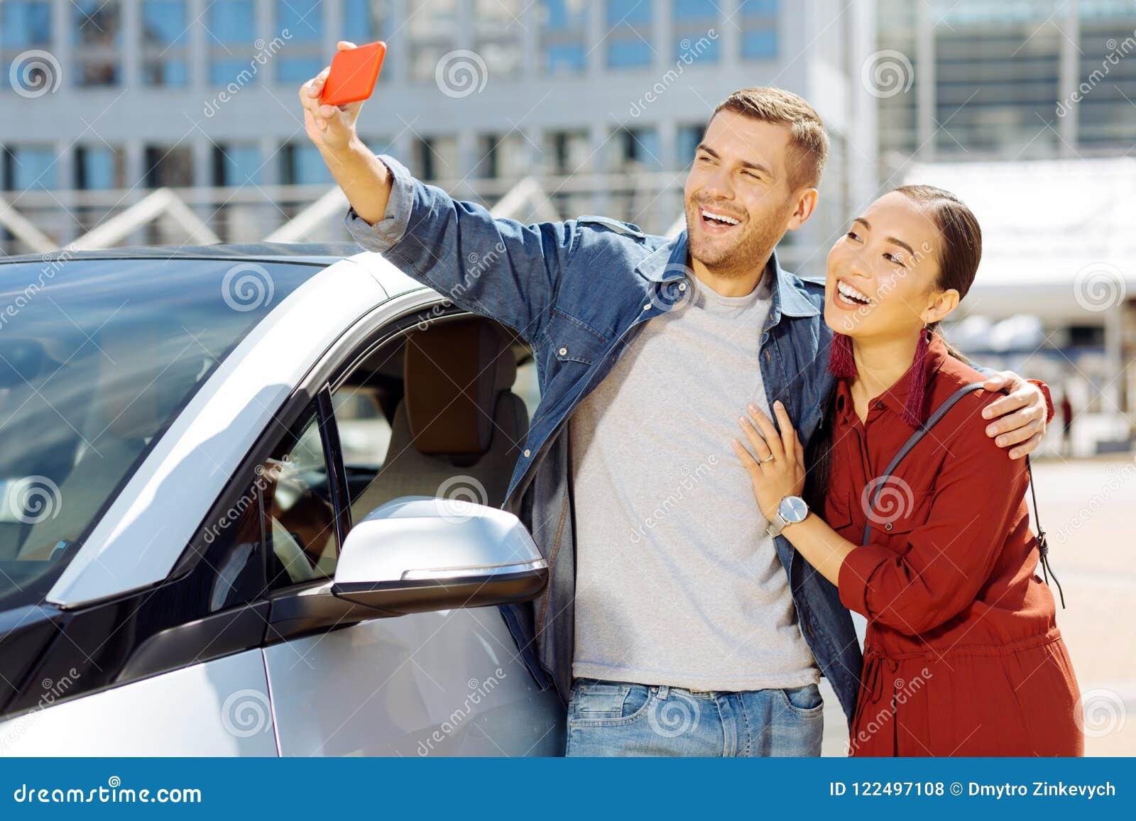 Rozochocona szczęśliwa para bierze selfies