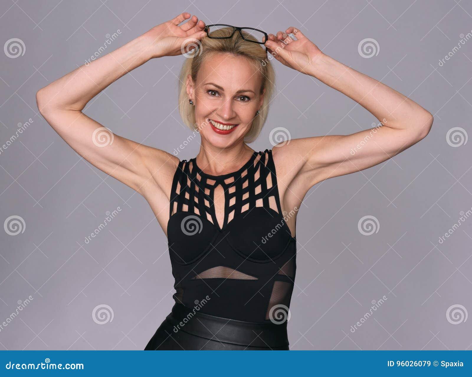 Rozochocona uśmiechnięta w średnim wieku kobieta jest ubranym szkła