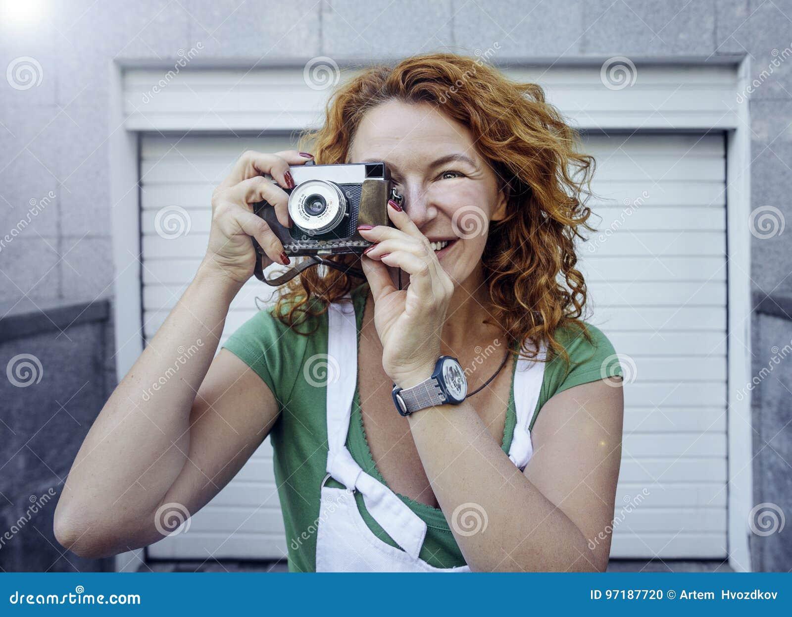 Rozochocona w średnim wieku dama używa rocznik kamerę Dzień, plenerowy