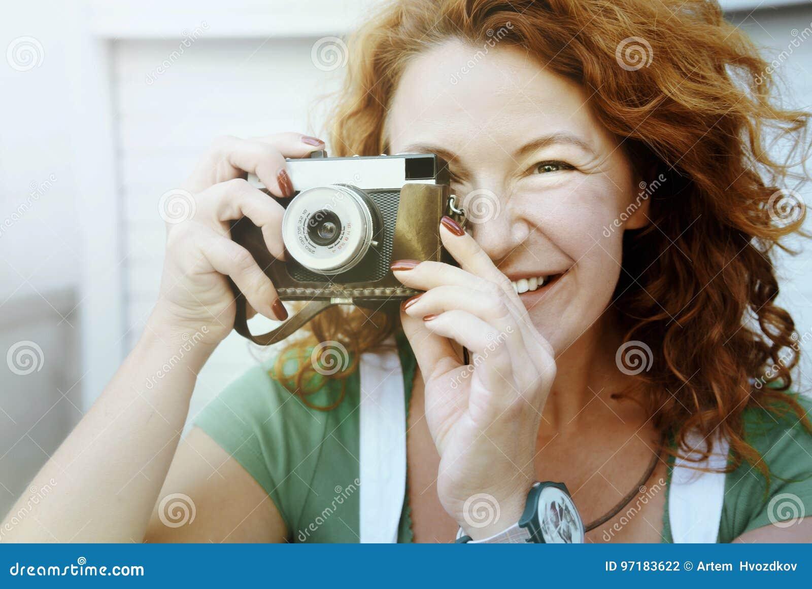 Rozochocona w średnim wieku dama używa rocznik kamerę Dzień, plenerowy Szczęśliwa czerwona włosiana kobieta bierze obrazek na ret