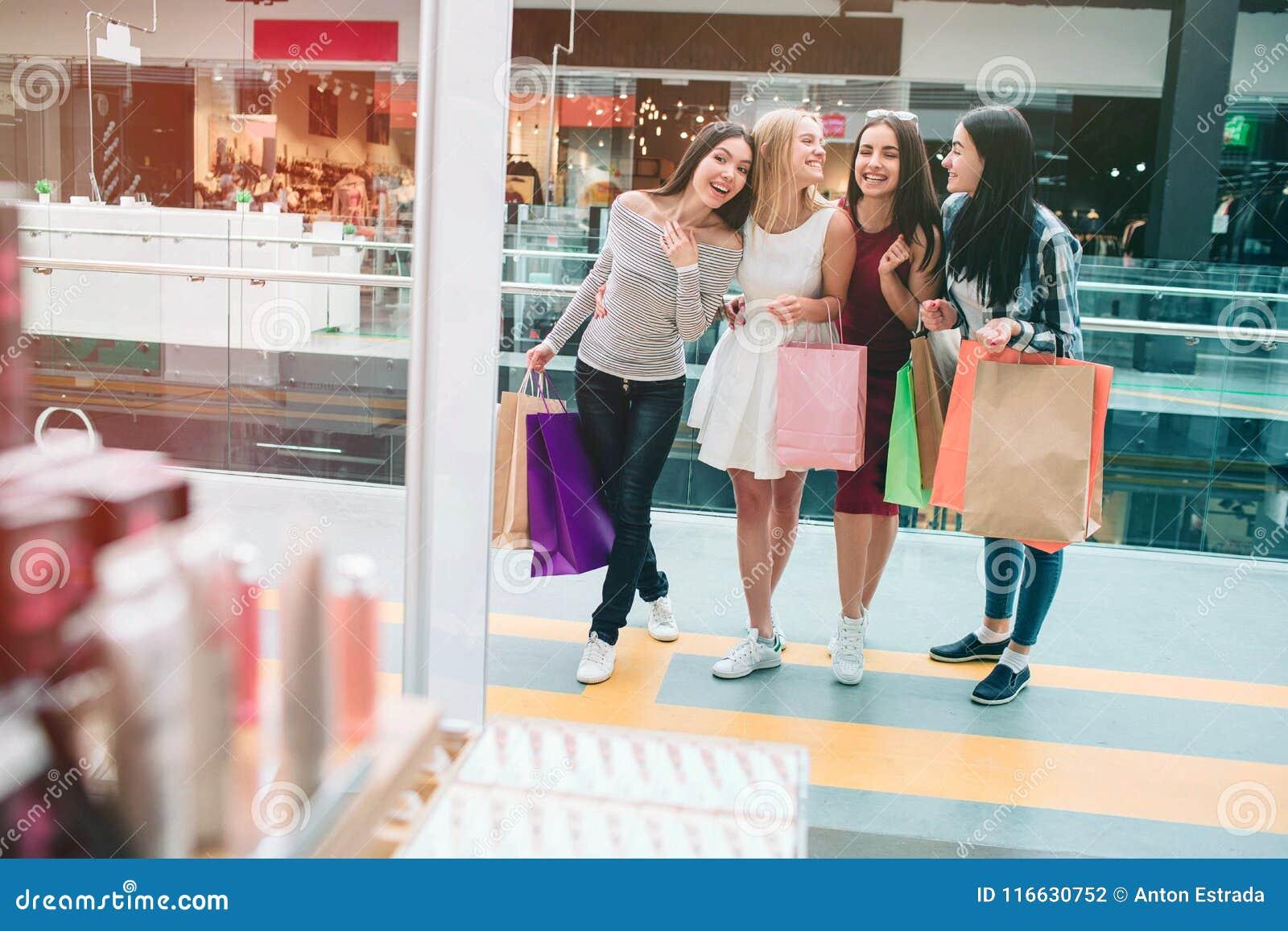 Rozochocone i błogie młode kobiety są trwanie przy wejściem sklep i patrzeć wśrodku go Są bardzo szczęśliwi i