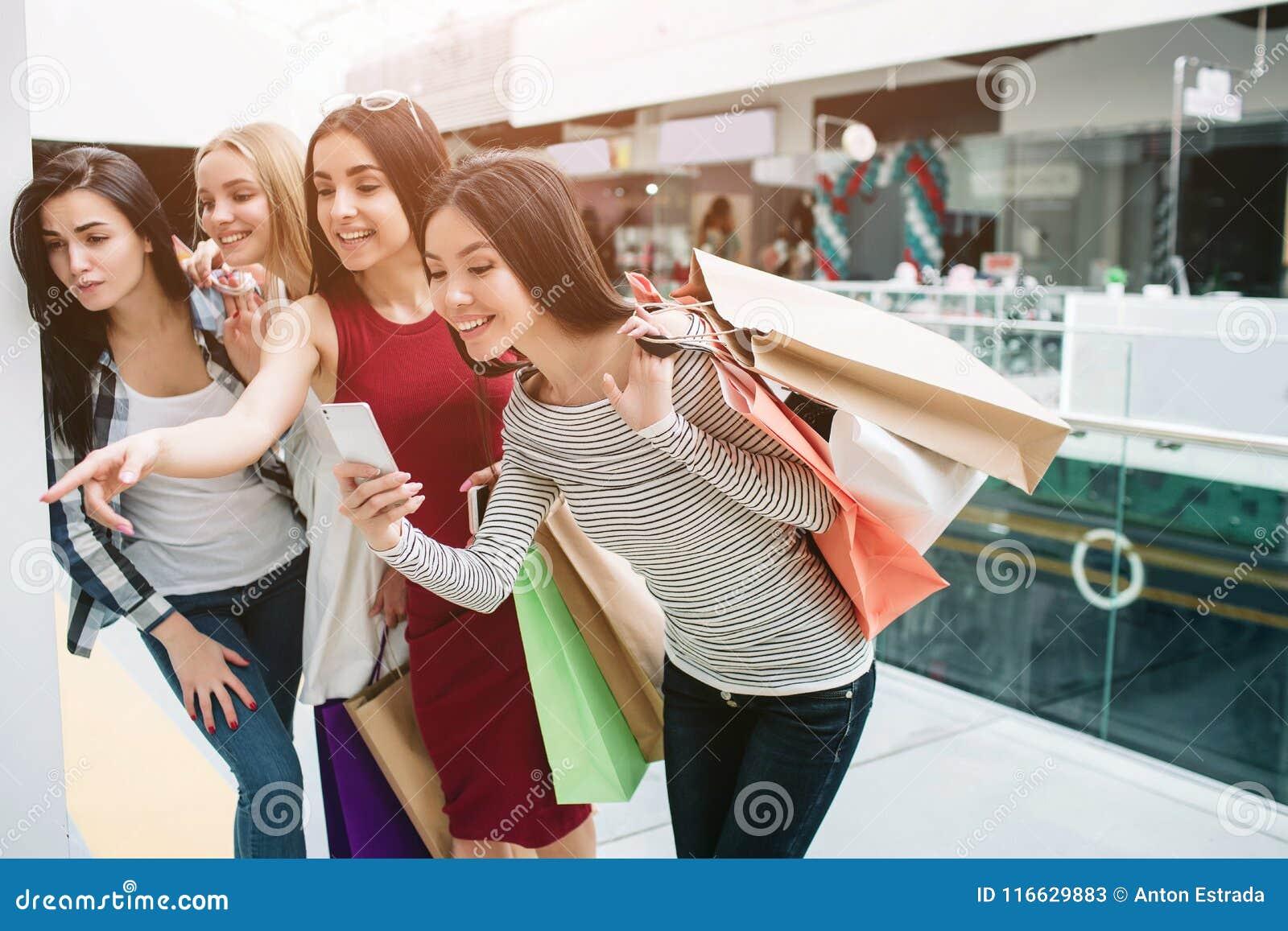 Rozochocone i szczęśliwe dziewczyny stoją jeden po inny i patrzeją w dół Dziewczyna w czerwieni sukni wskazuje podczas gdy azjaty