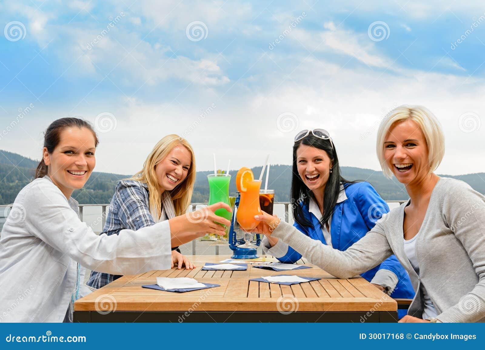 Kobiety wznosi toast koktajl restauraci plenerowego taras