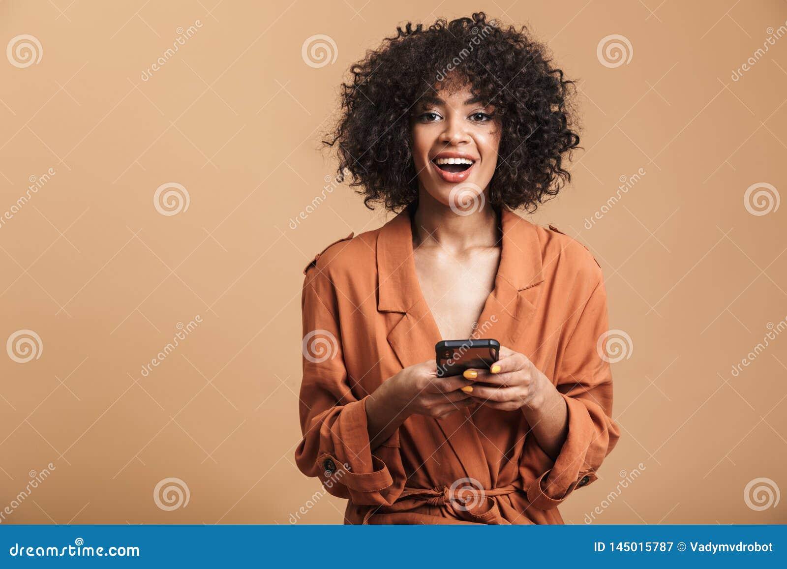 Rozochocony ładny afrykański kobiety mienia smartphone i patrzeć kamerę