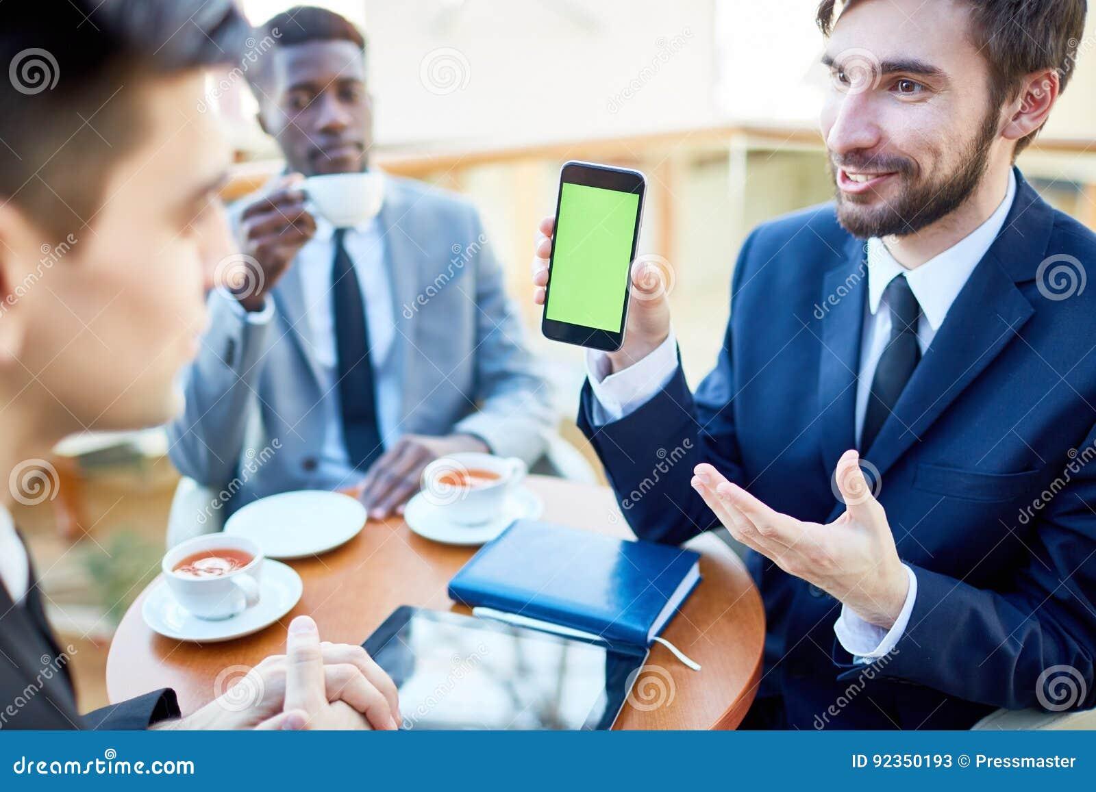 Rozochocony biznesmen Pokazuje wiszącą ozdobę App koledzy