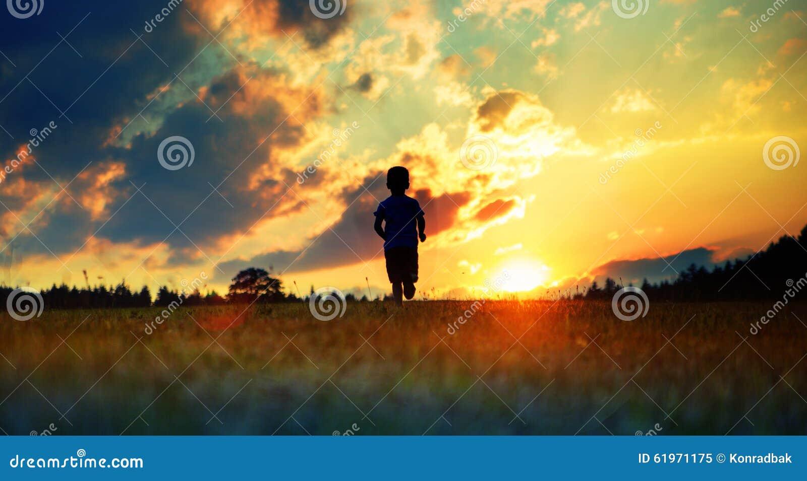 Rozochocony chłopiec bieg w kierunku zmierzchu