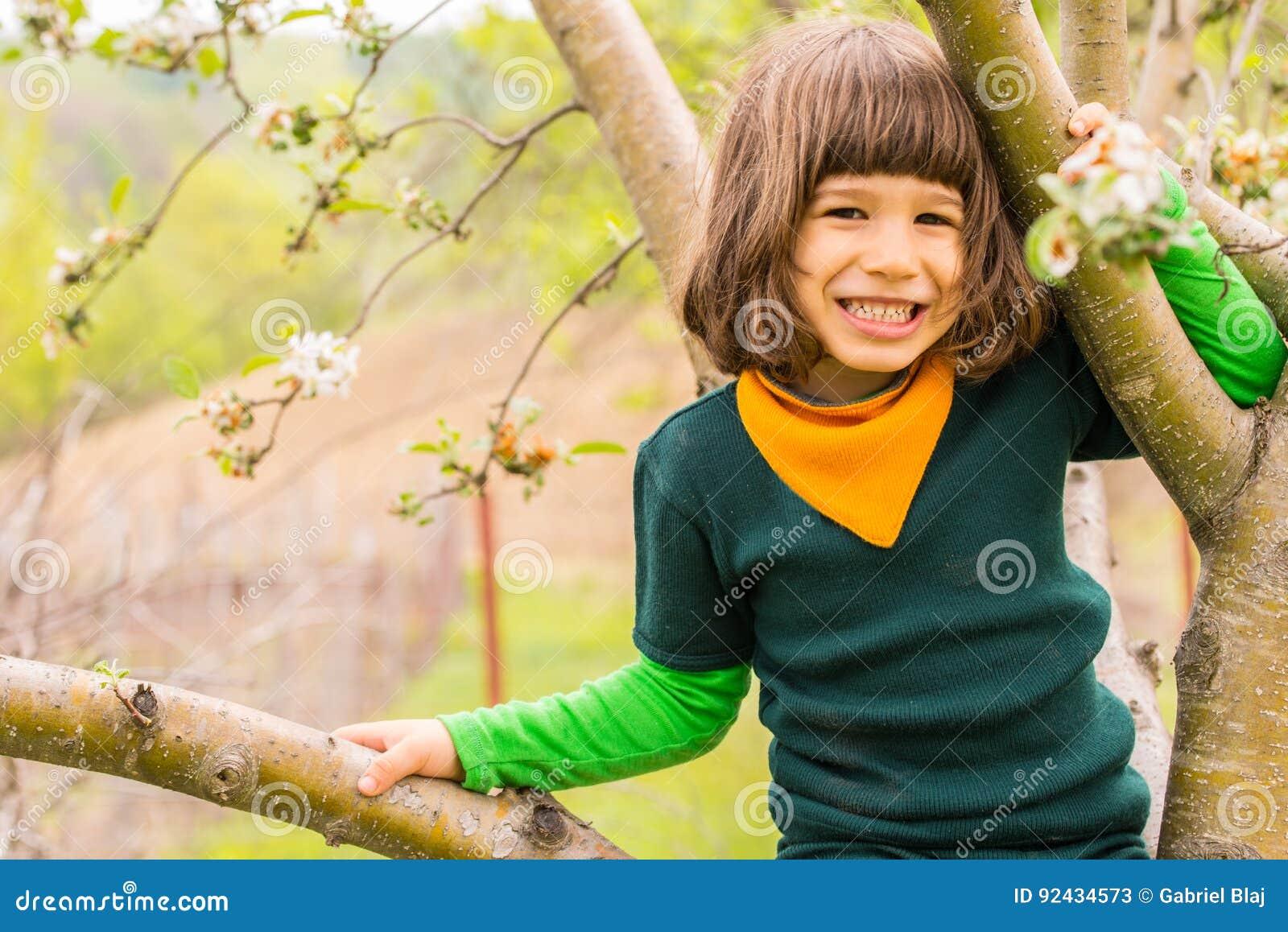 Rozochocony chłopiec wspinaczki drzewo