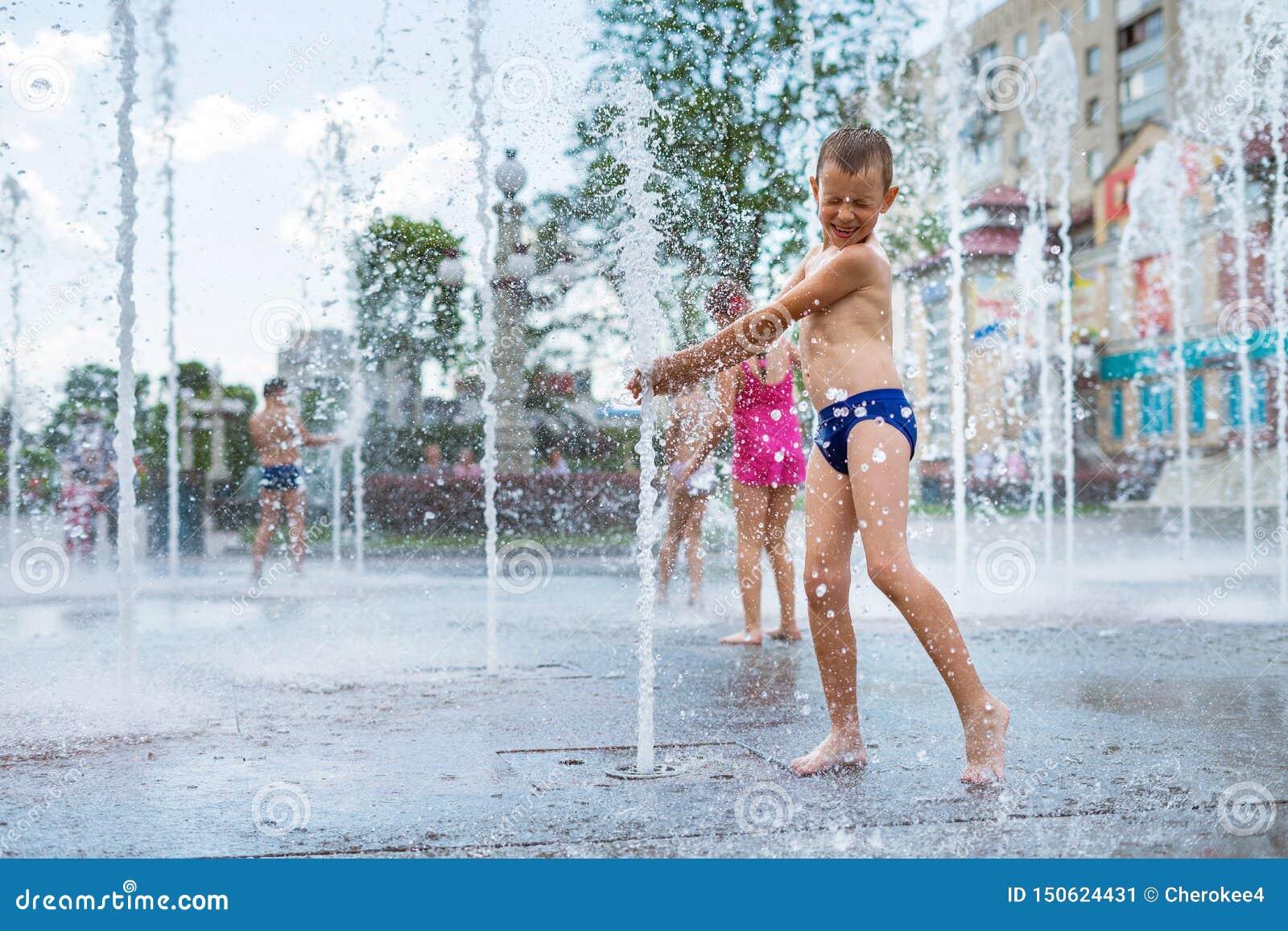 Rozochocony dziecko bawić się w wodnej fontannie i cieszy się chłodno strumienie woda w lato gorącym dniu
