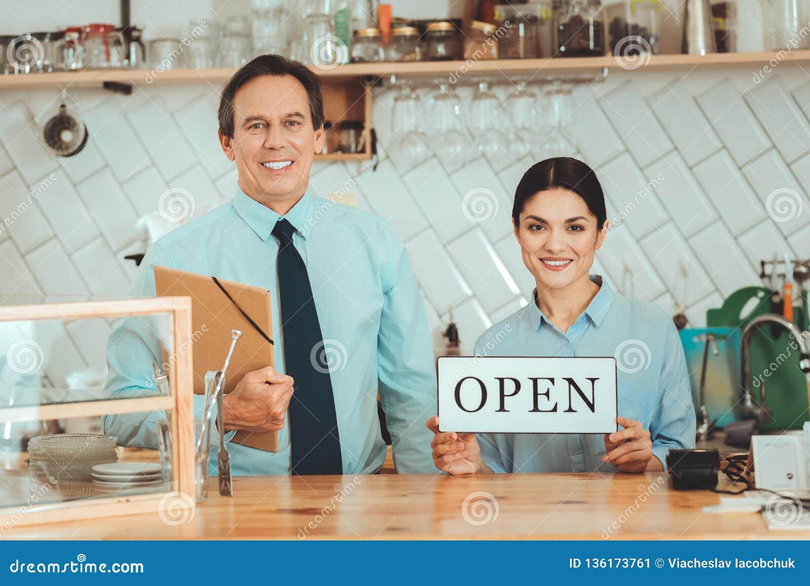 Rozochocony mężczyzna i kobieta reklamuje ich nowego zaczynamy w górę