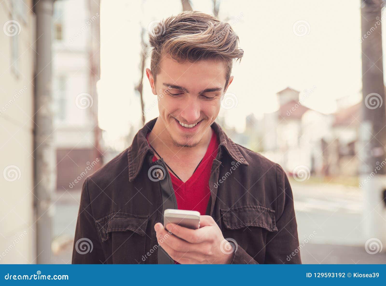 Rozochocony mężczyzna używa telefon komórkowego outdoors