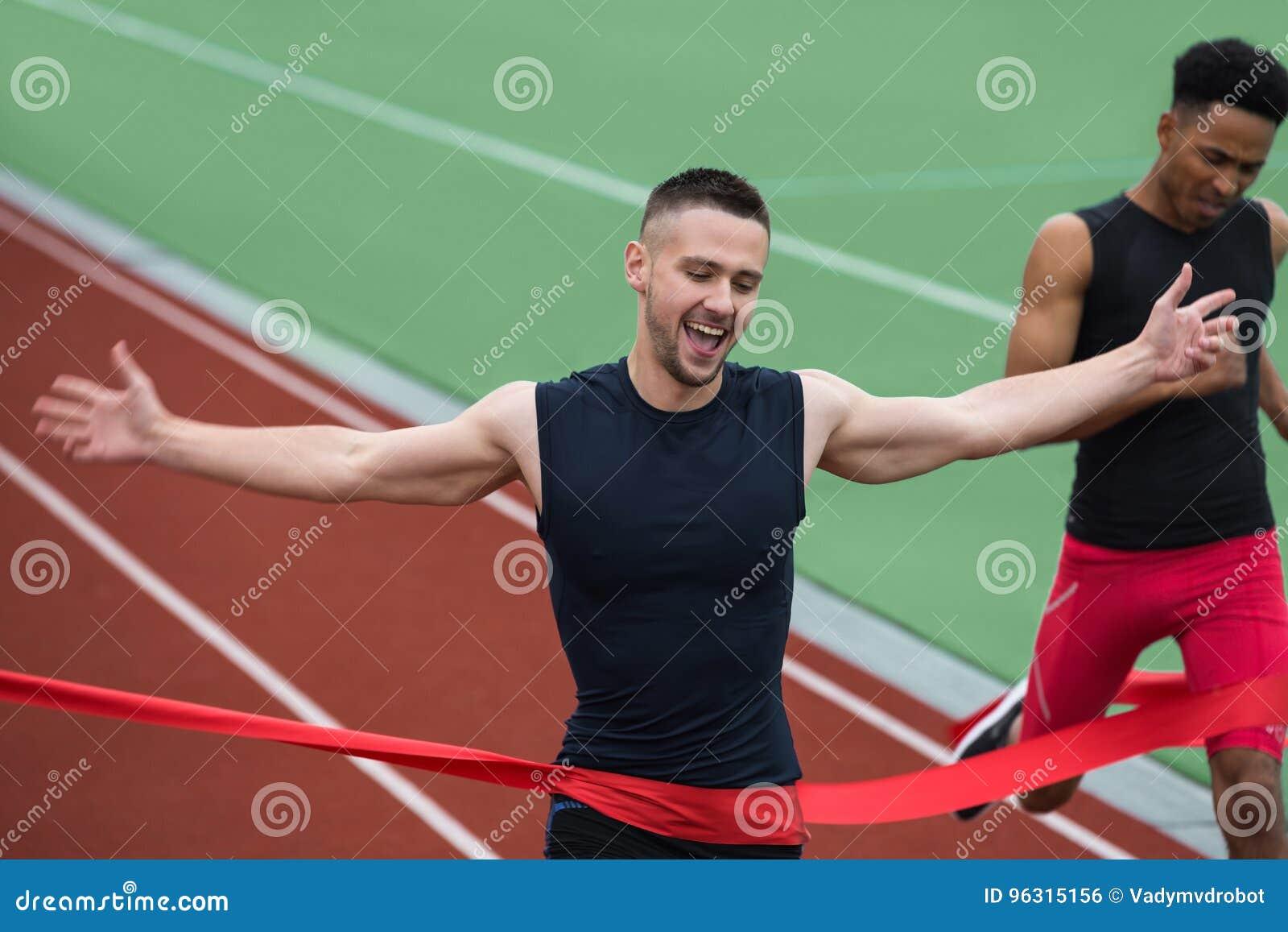 Rozochocony młody atleta mężczyzna mety skrzyżowanie