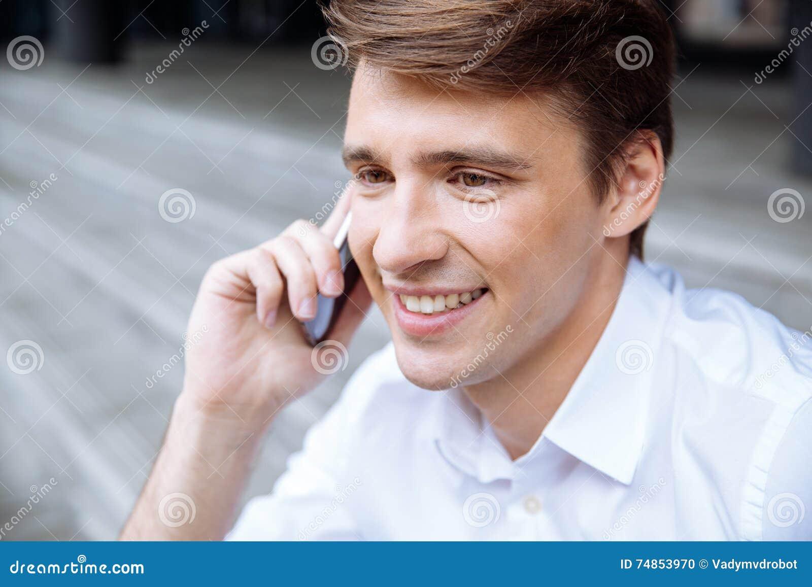 Rozochocony młody biznesmen opowiada na telefonie komórkowym