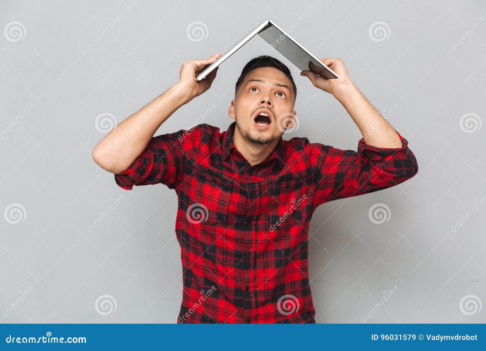 Rozochocony młody człowiek w szkockiej kraty sirt mienia laptopu koszt stały